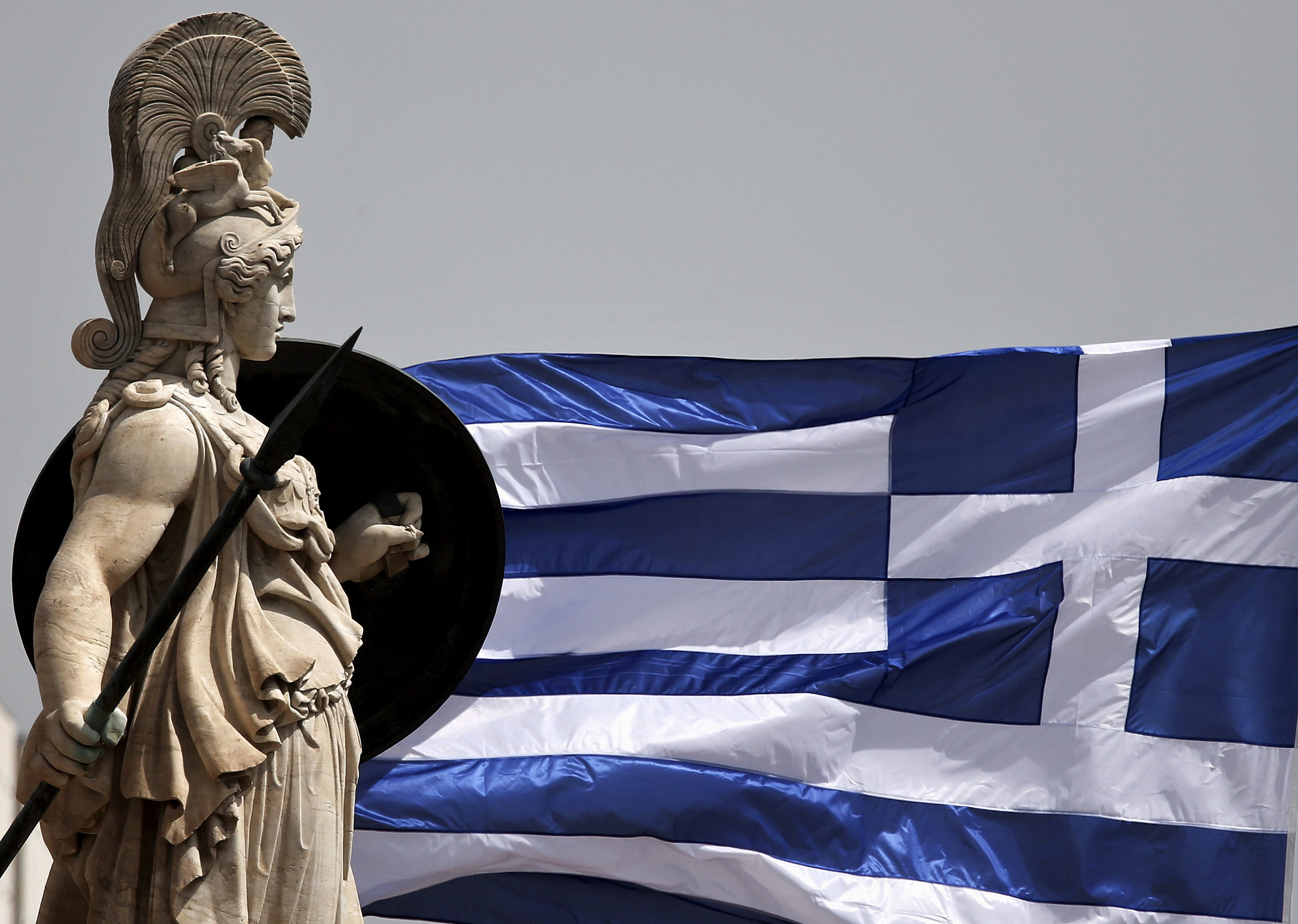 A Greek national flag flutters next to a statue of ancient Greek goddess Athena, in Athens May 21, 2015. Greek Finance Minister Yanis Varoufakis has raised a fresh furore by telling a newspaper that he taped a confidential meeting of euro zone finance ministers, drawing criticism that he was undermining Greece's efforts to secure aid from lenders.