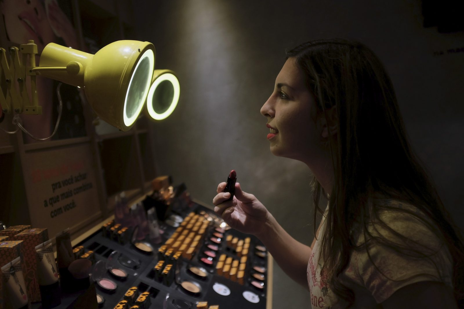 A woman checks lipstick applied on her lip, inside of a cosmetics shop in Sao Paulo, Brazil August 13, 2015. From cigarettes to lipstick to sandals, exports have emerged as a silver lining for Brazilian consumer goods companies that are suffering the worst domestic slump in over a decade. With Brazil's currency, the real, at a 12-year low, foreign sales have kept several companies in the black, helping them outperform rivals focused on the local market, according to a Reuters analysis of second-quarter earnings.
