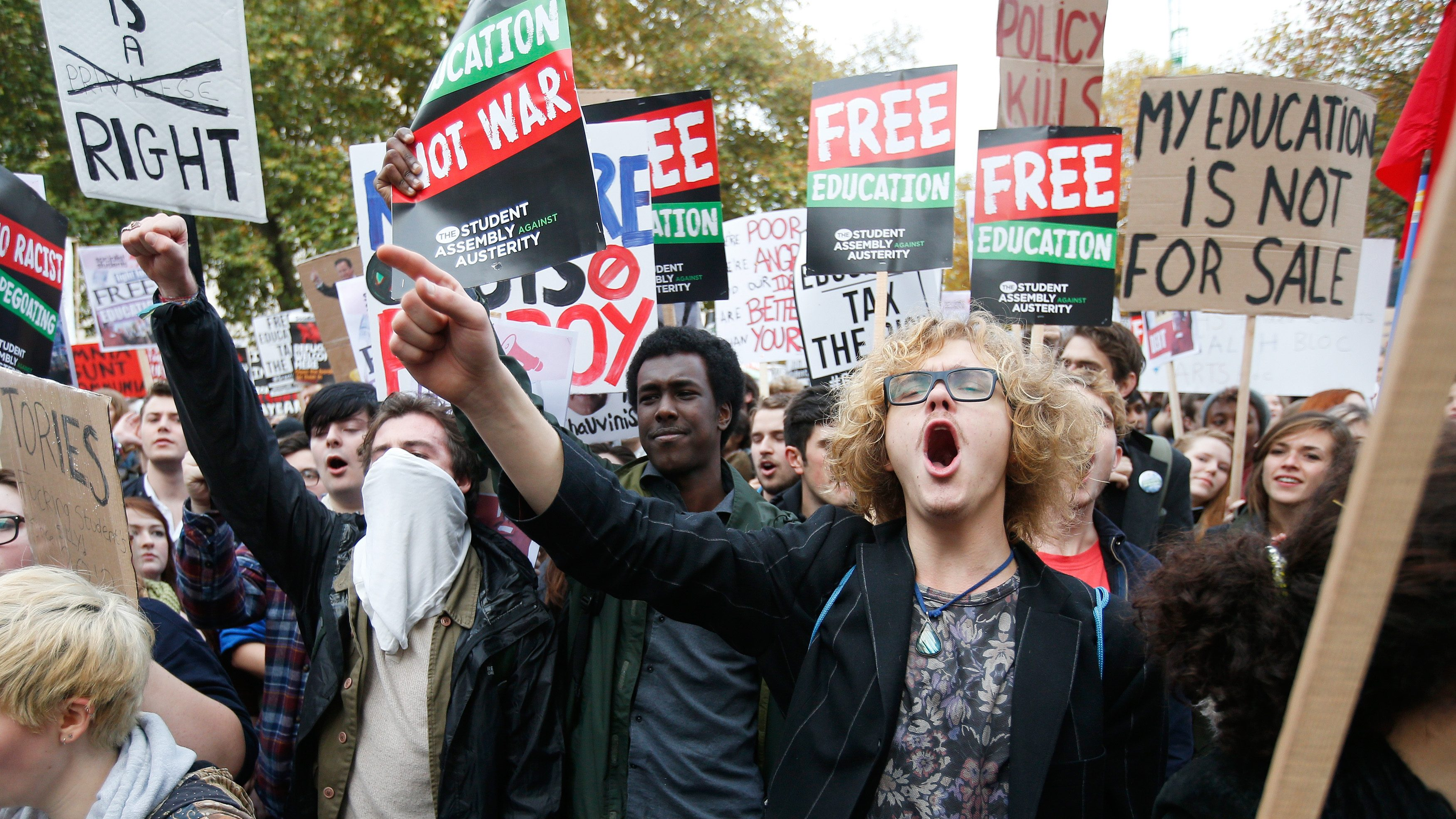 Students shout slogans and hold banners during a demonstration to protest against cuts to grants, in London
