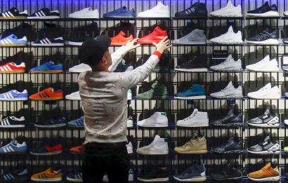 A shop assistant works at the Adidas flagship store in Berlin, Germany, January 20, 2016. A combination of new and retro sneaker styles will keep driving growth at Adidas's fashion business and help attract more sports fans too, the head of the German firm's Originals unit said in an interview. Picture taken January 20, 2016. REUTERS/Hannibal Hanschke - RTX23CBS