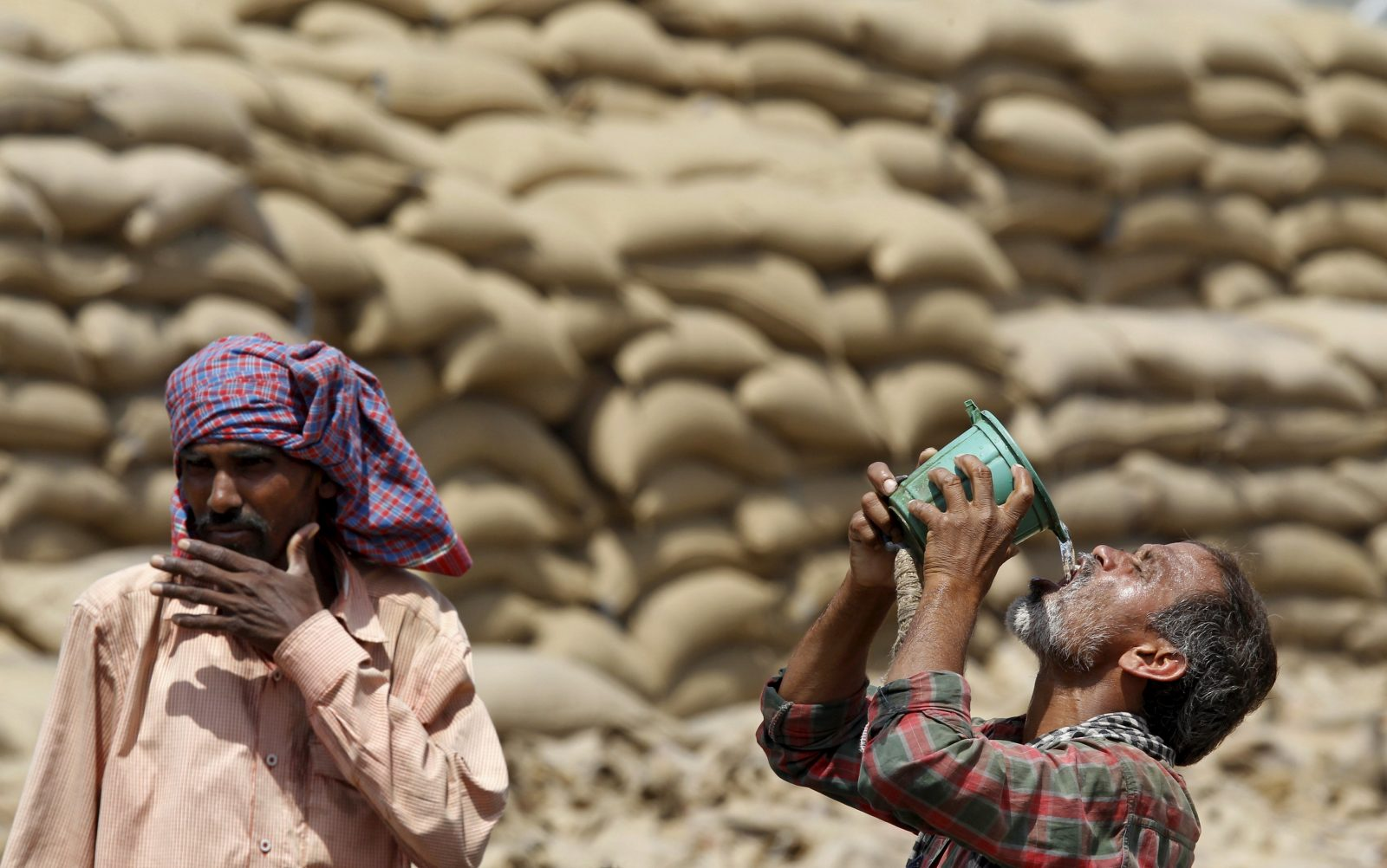 A labourer drinks water as another looks on, on a hot summer day at a grain market in Chandigarh, India April 19, 2016. REUTERS/Ajay Verma - RTX2AMML