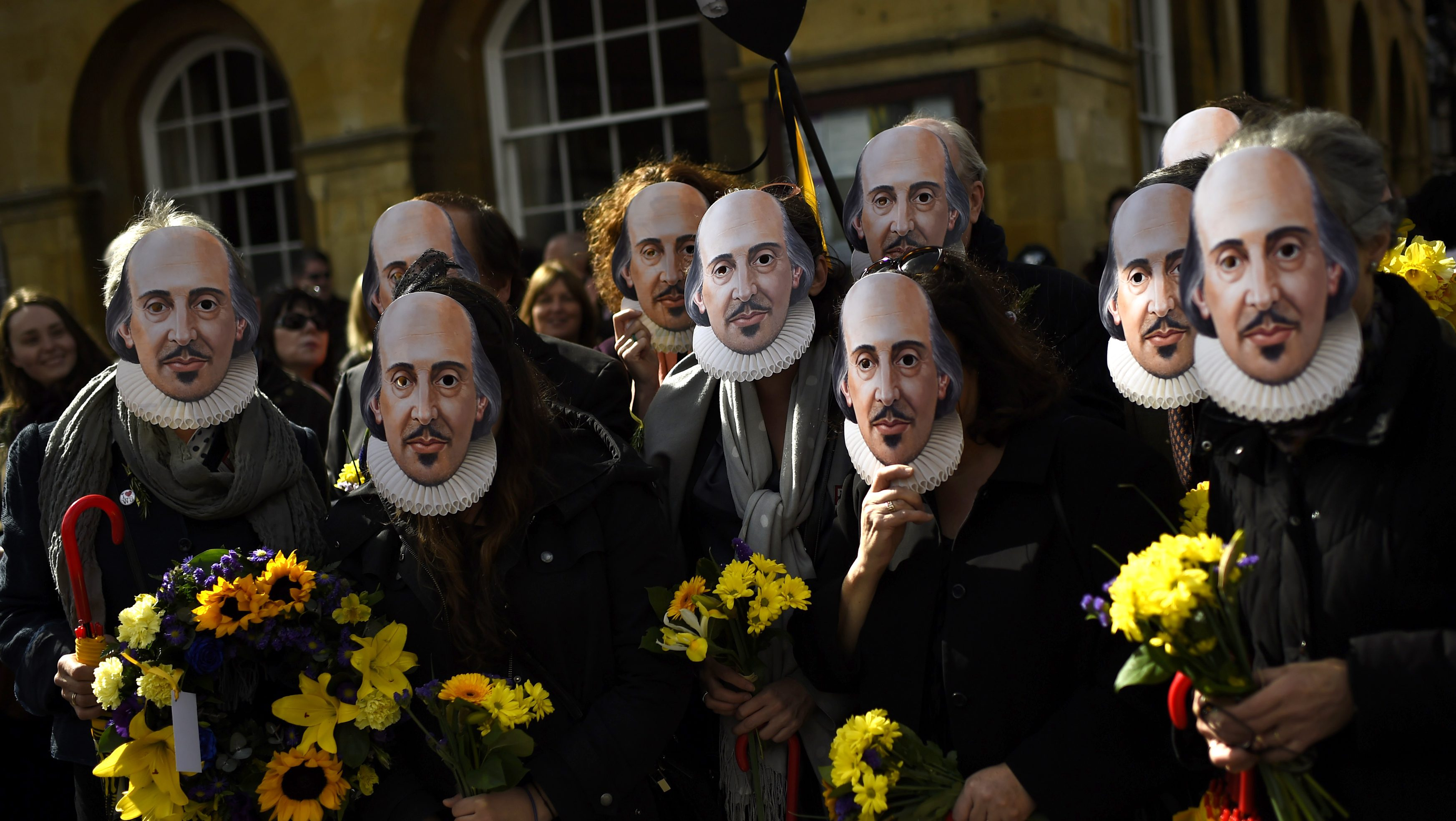 People hold up face masks with William Shakespeare's portrait during celebrations to mark the 400th anniversary of the playwright's death in the city of his birth, Stratford-Upon-Avon, Britain, April 23, 2016. REUTERS/Dylan Martinez - RTX2BAQO