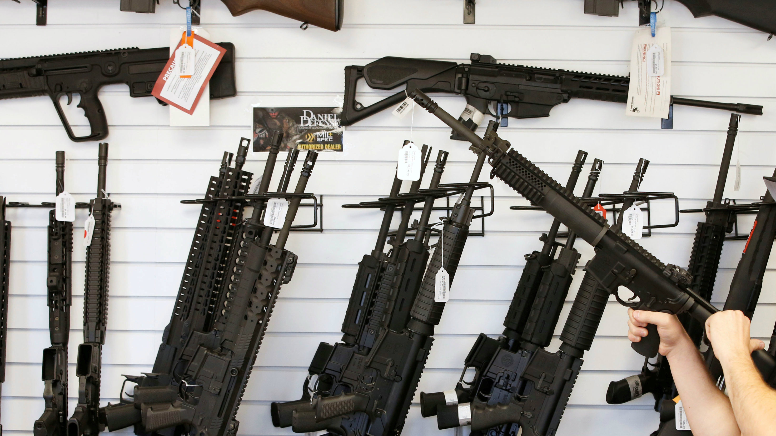 """Salesman Ryan Martinez clears the chamber of an AR-15 at the """"Ready Gunner"""" gun store In Provo"""