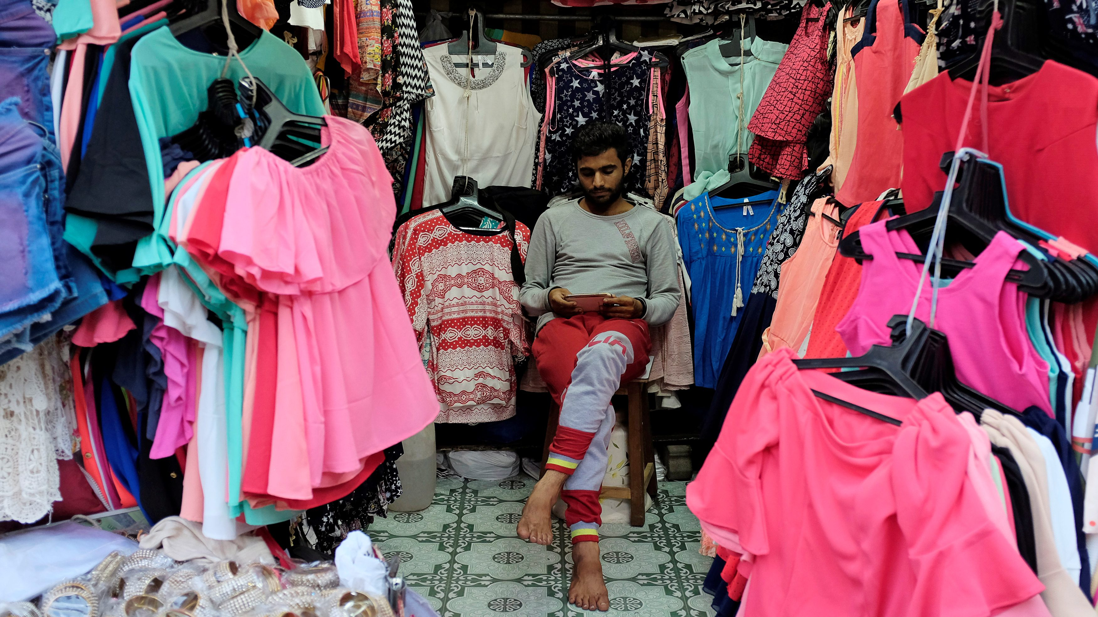 A vendor selling clothes looks at his mobile phone as he waits for customers at a market in Mumbai, India, August 30, 2016. Picture taken August 30, 2016. REUTERS/Danish Siddiqui - RTX2NO6V