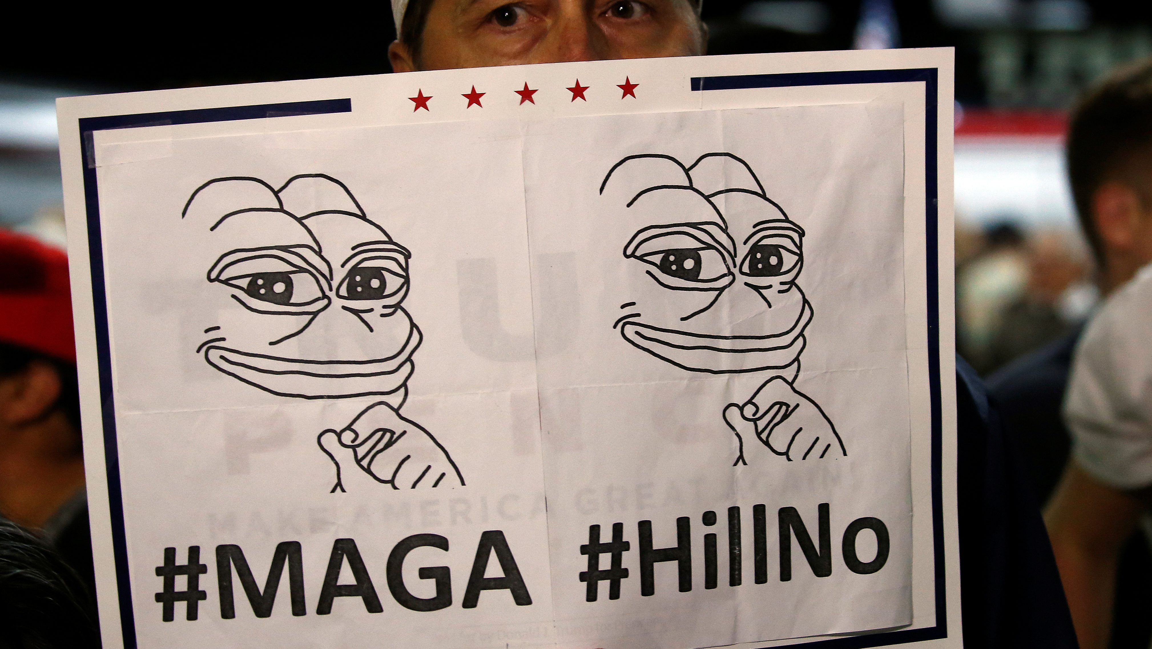 A man hides his face behind a Pepe the Frog sign after Republican presidential nominee Donald Trump spoke at an airport campaign rally in Albuquerque, New Mexico, U.S. October 30, 2016.