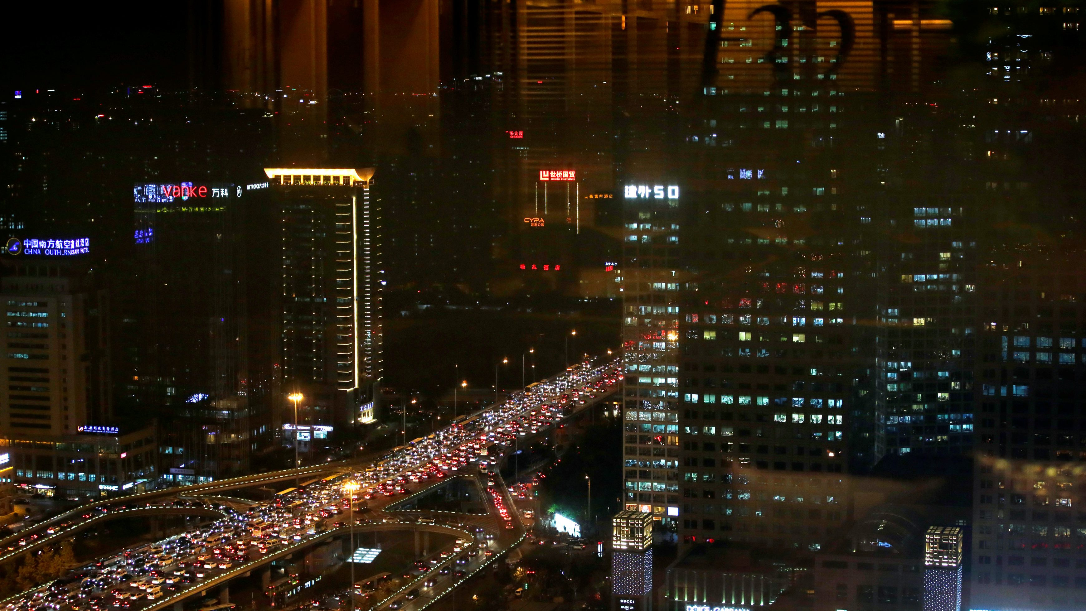 Vehicles are seen through a window as they drive on Guomao Bridge during rush hour in Beijing, China, November 7, 2016. REUTERS/Jason Lee - RTX2SAOY