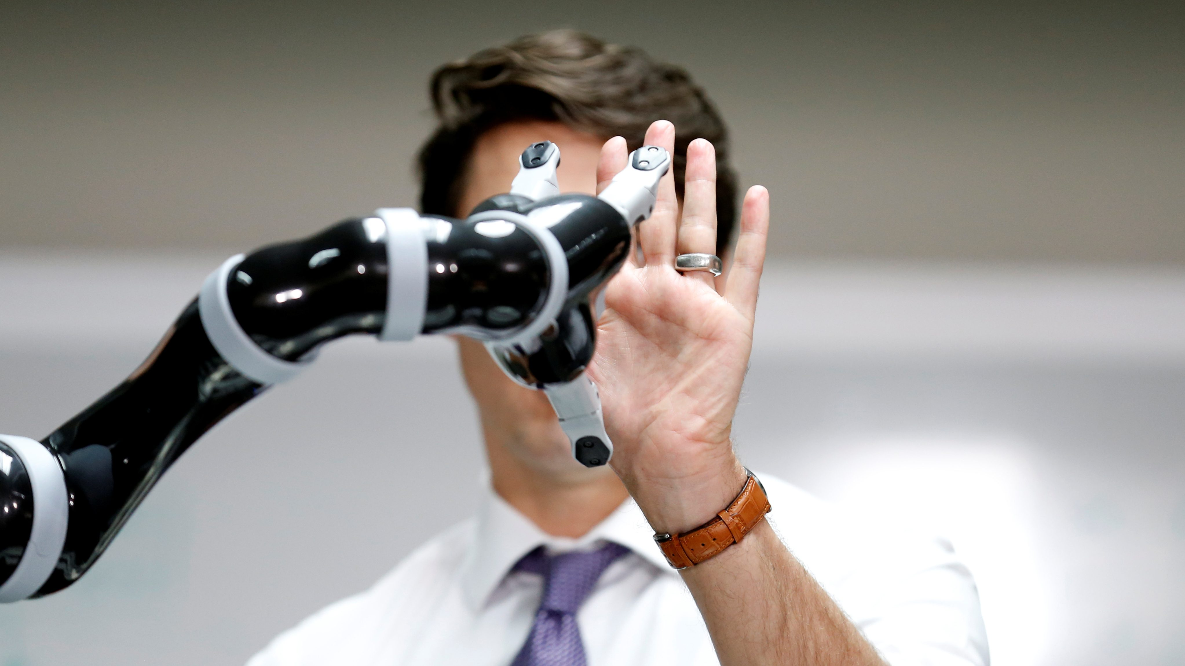 Canadian Prime Minister Justin Trudeau high fives a robotic arm as he takes part in a robotics demonstration at Kinova Robotics in Boisbriand, Quebec, Canada March 24, 2017.  REUTERS/Christinne Muschi     TPX IMAGES OF THE DAY - RTX32L58