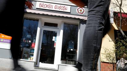 "Pedestrian walk past the ""Broken English"" store in Berlin"