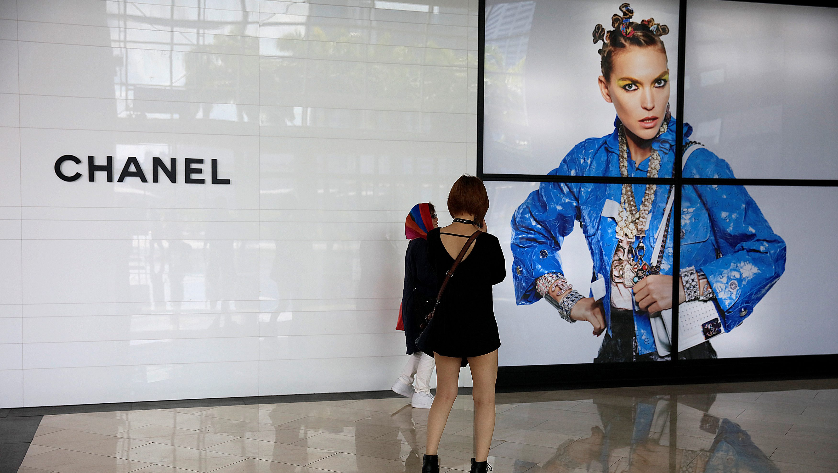 Women take photos in front of a Chanel shop in Singapore May 19, 2017. REUTERS/Thomas White - RTX36K4C