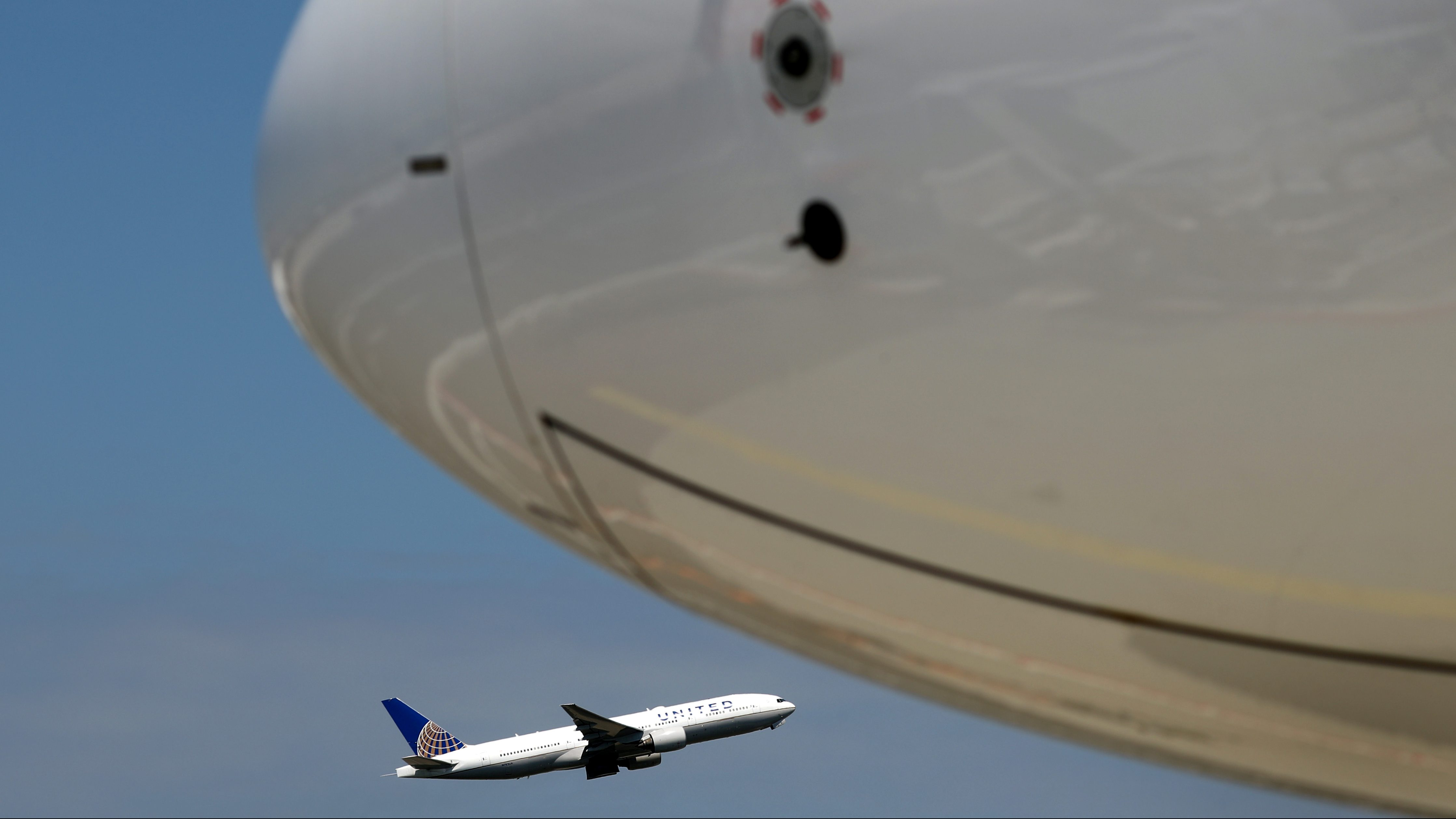 A plane of United airlines takes off next to an Airbus A350-900 of Ethiopian Airlines