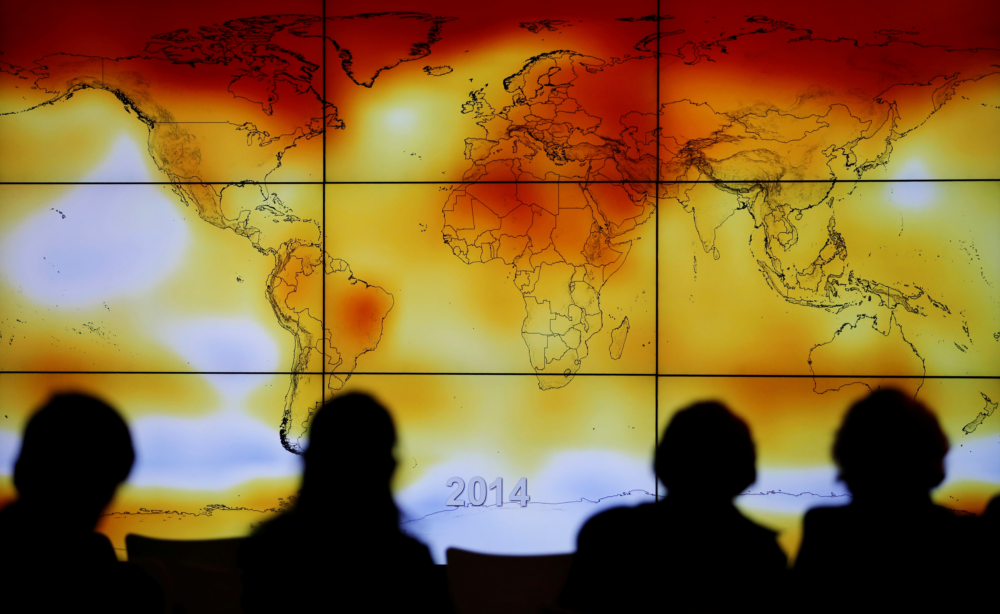 Participants look at a screen projecting a world map with climate anomalies during the World Climate Change Conference 2015 (COP21) at Le Bourget