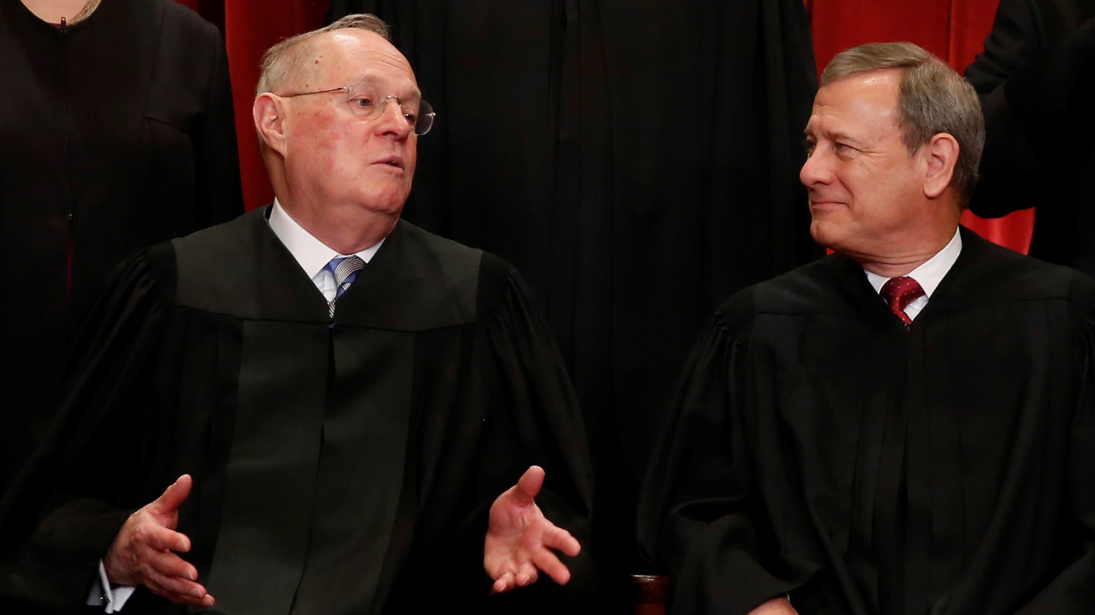 Chief justice John Roberts (right) talks with justice Anthony Kennedy (left) during a photo shoot at the United States Supreme Court.