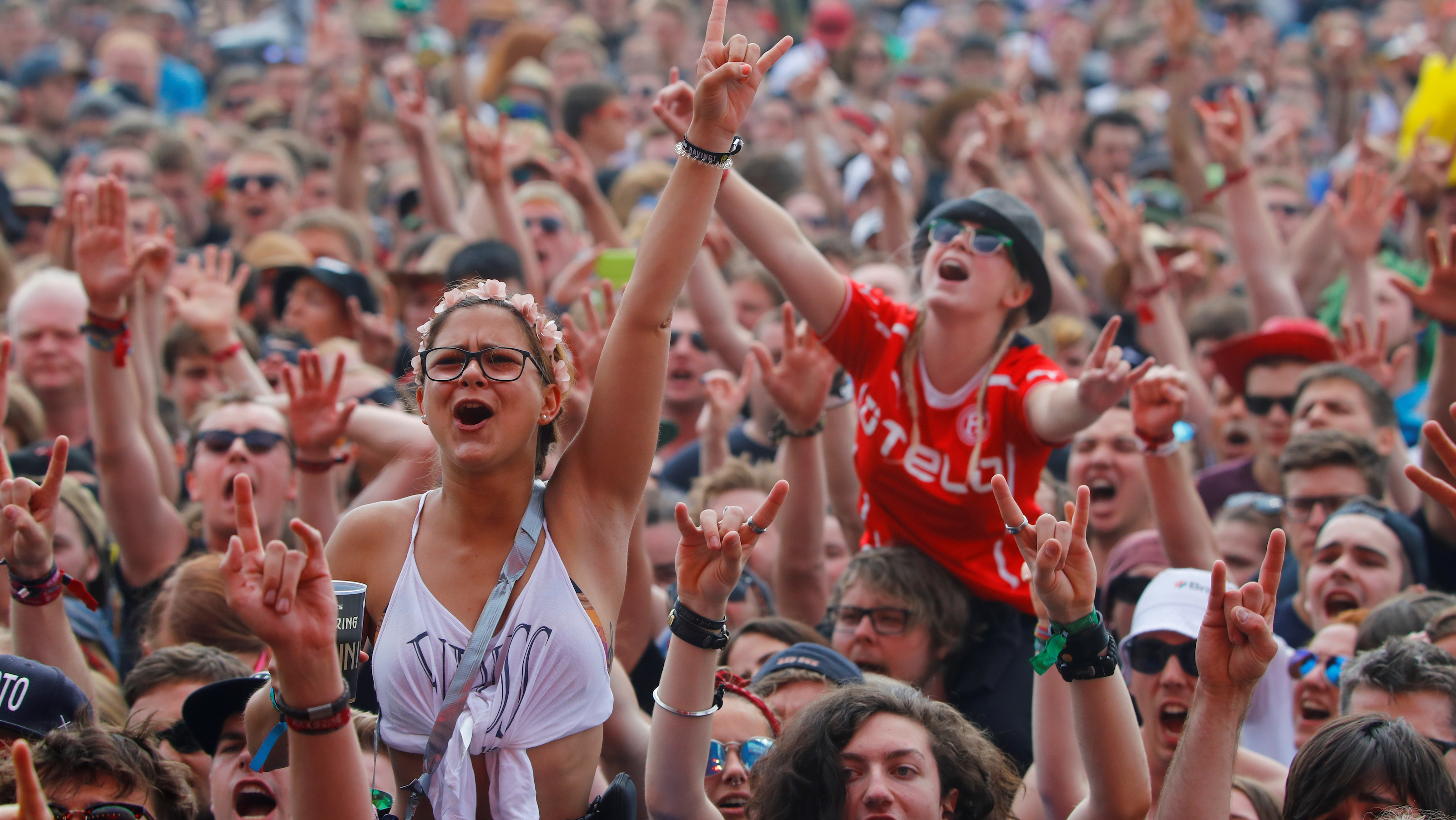 "Festival goers cheer for a rock band at the open-air weekend ""Rock am Ring"" concert at Germany's Formula One race track Nuerburgring, Germany June 3, 2017. REUTERS/Wolfgang Rattay - RTX38TD4"