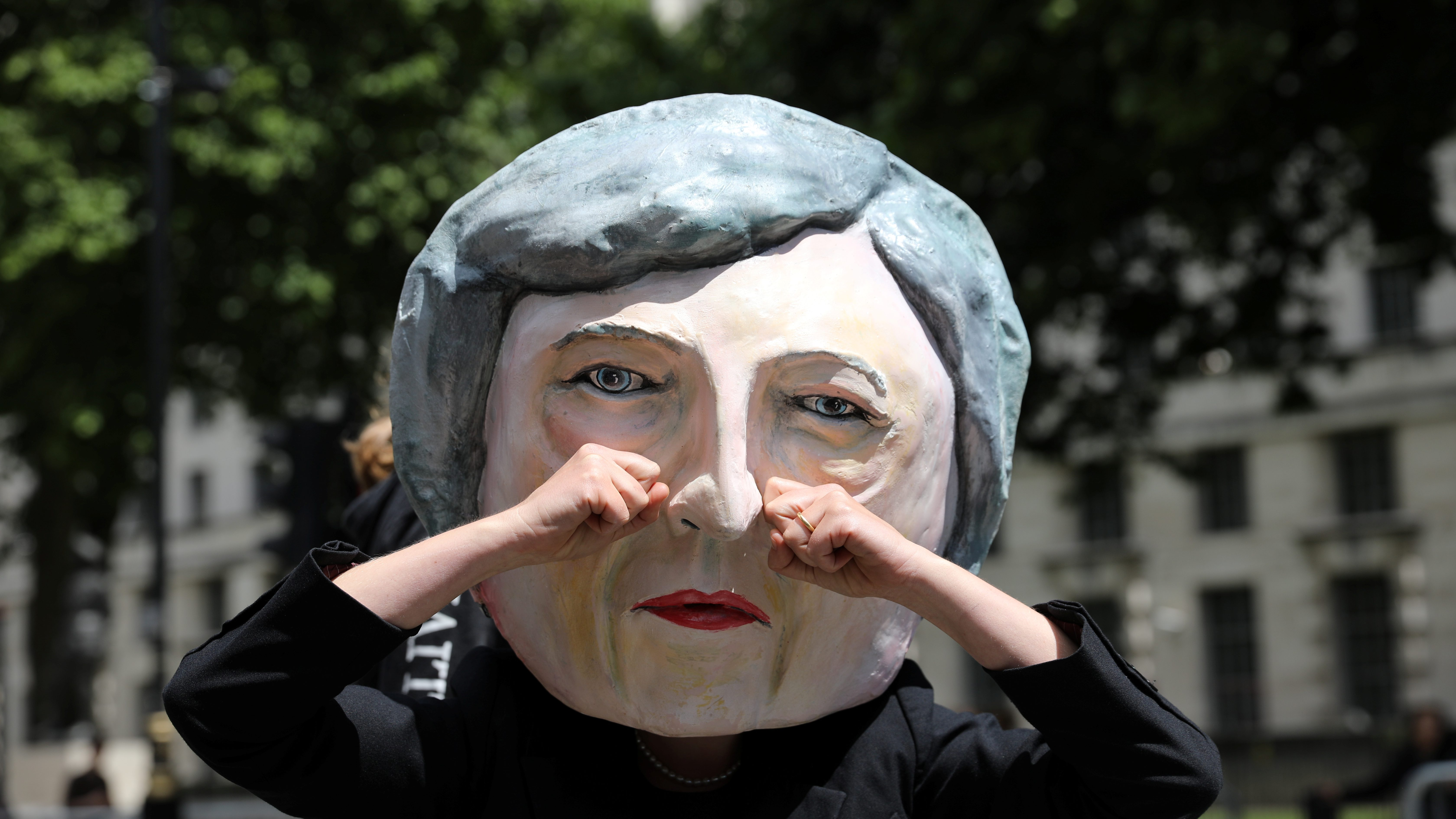 A protestor wears a Theresa May mask