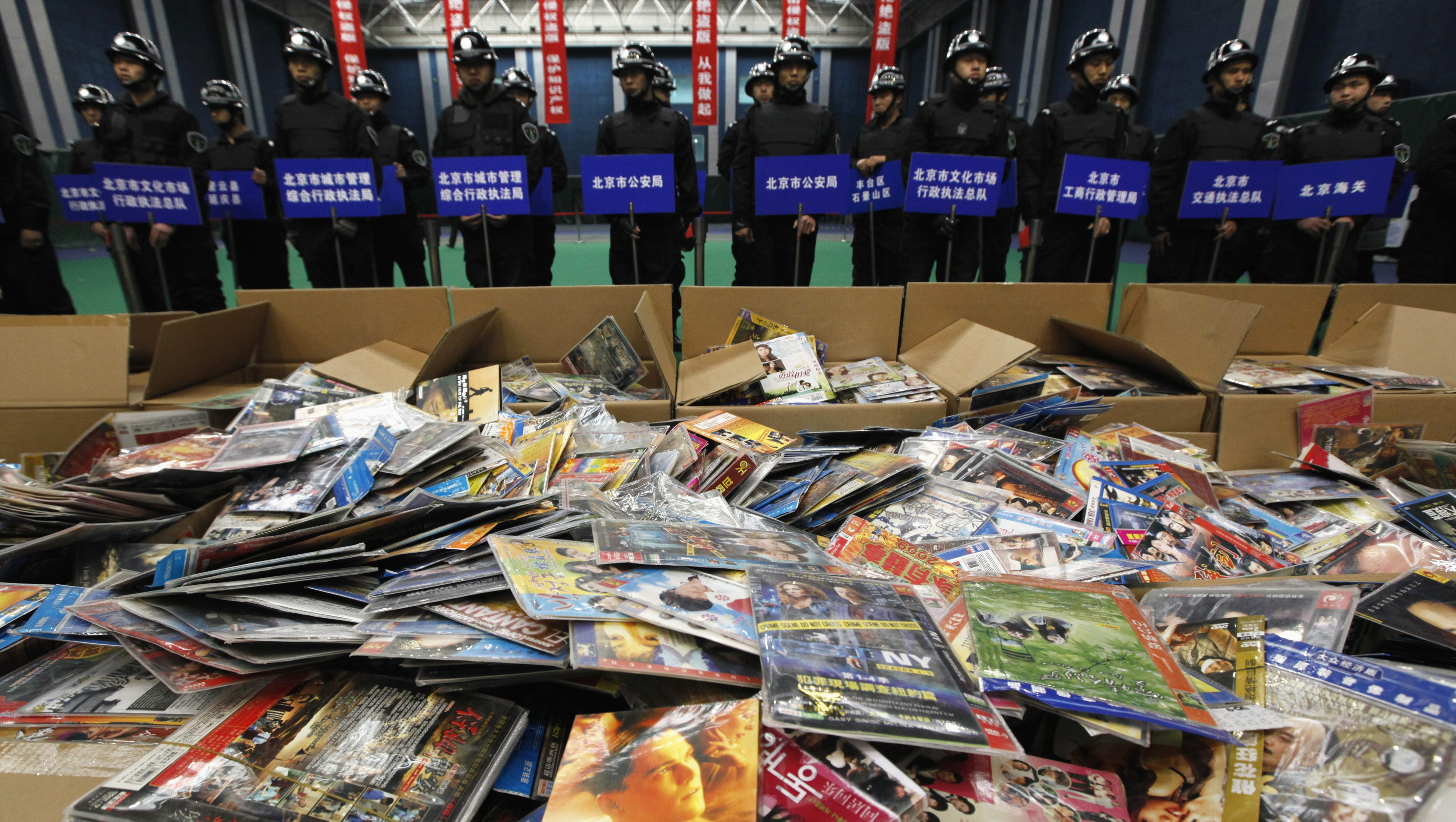 Security guards stand next to pirated DVDs which will be destroyed during a campaign against the production and distribution of porn and pirated publications, during a photo opportunity inside a gymnasium in Beijing January 10, 2011.