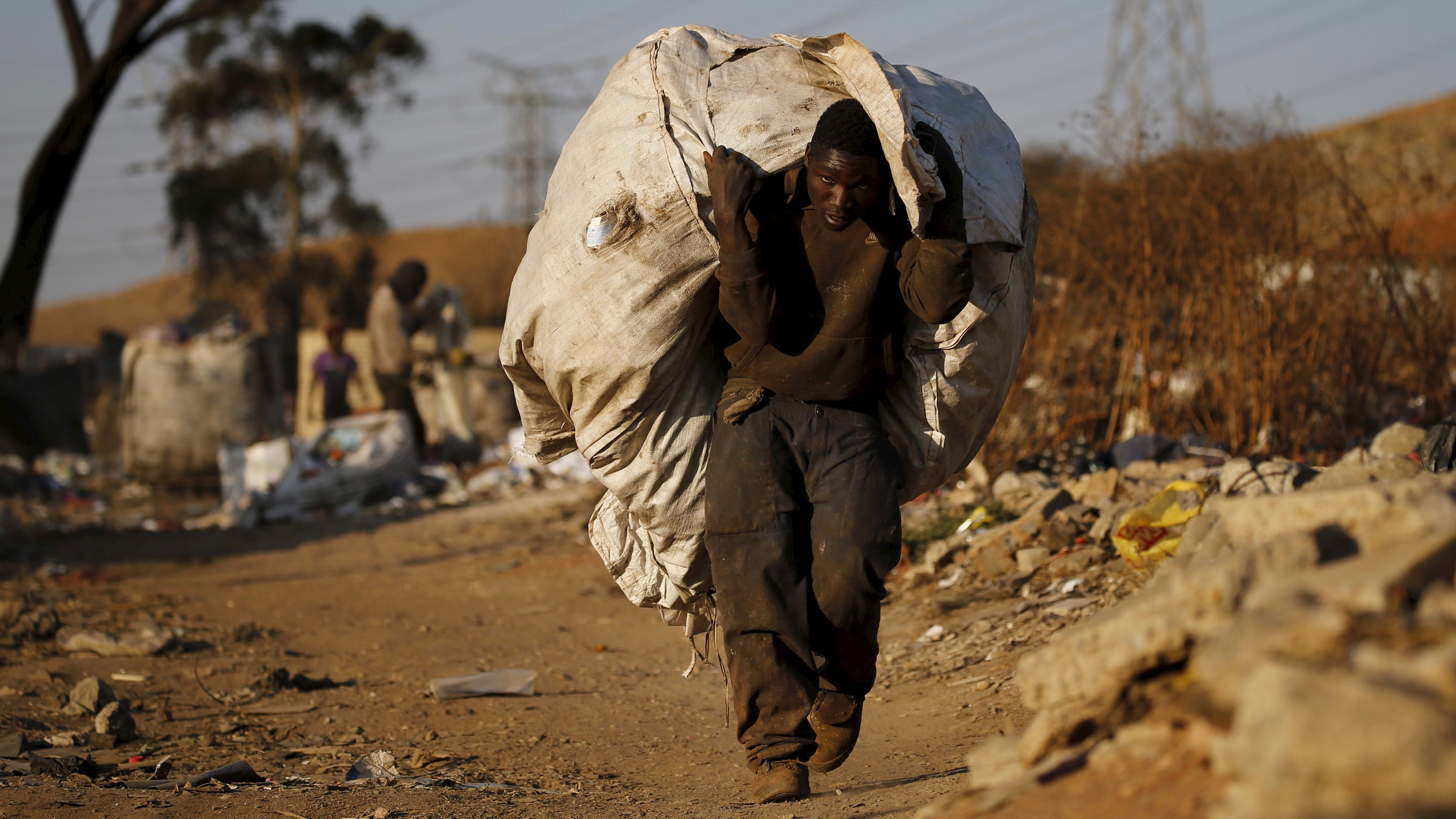 An unemployed man carries a bag full of recyclable waste material which he sells for a living, in Daveland near Soweto, South Africa August 4, 2015. REUTERS/Siphiwe Sibeko  - RTX1N1MB