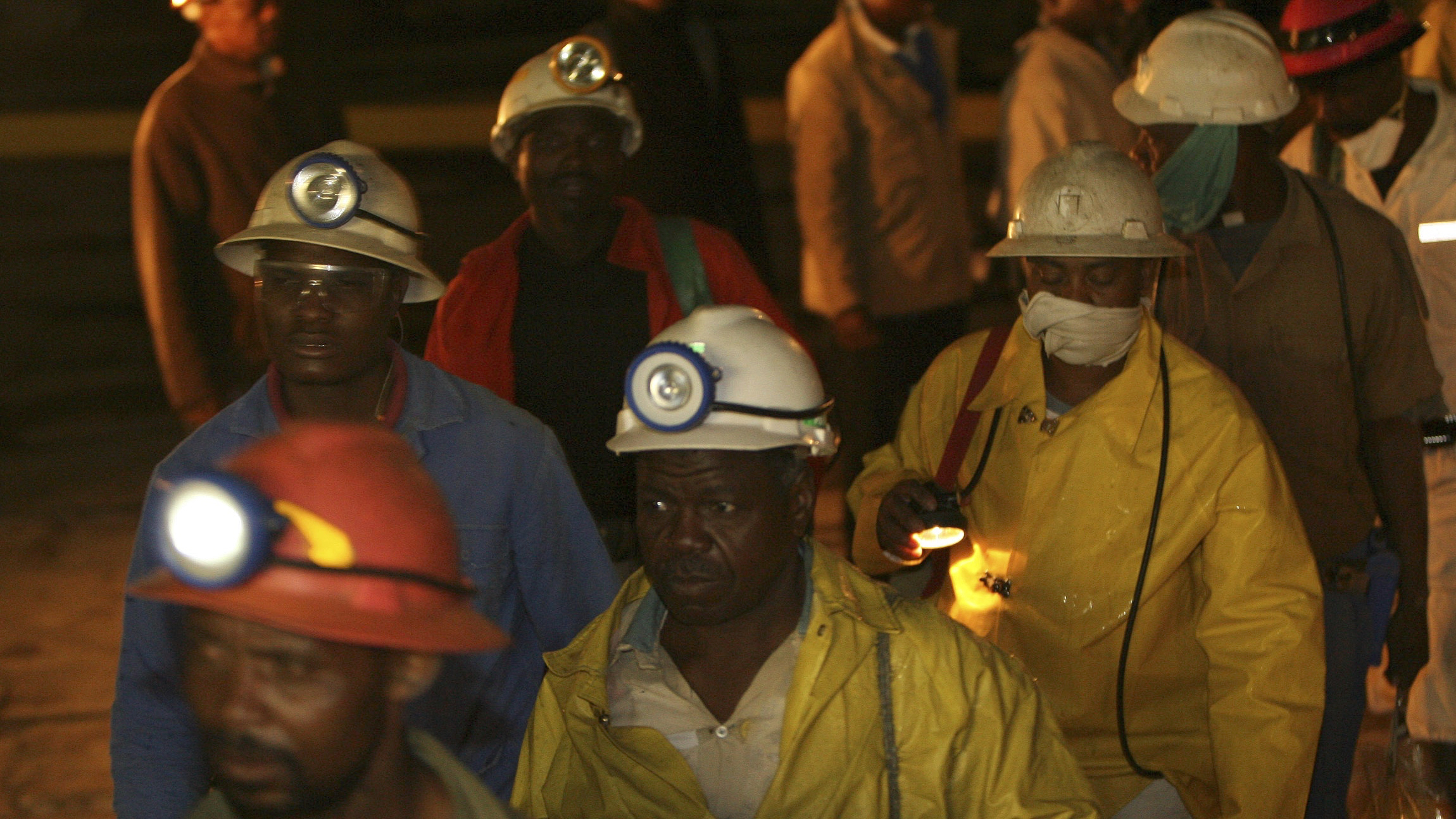 Harmony Gold miners appear on the surface after being trapped underground for more than 10 hours at a mine in Carltonville, west of Johannesburg, October 4, 2007. Rescue teams brought the first 450 miners out of 3,200 trapped underground in a South African gold mine to the surface early on Thursday, mine and union officials said. REUTERS/Siphiwe Sibeko  (SOUTH AFRICA) - RTR1UK5C