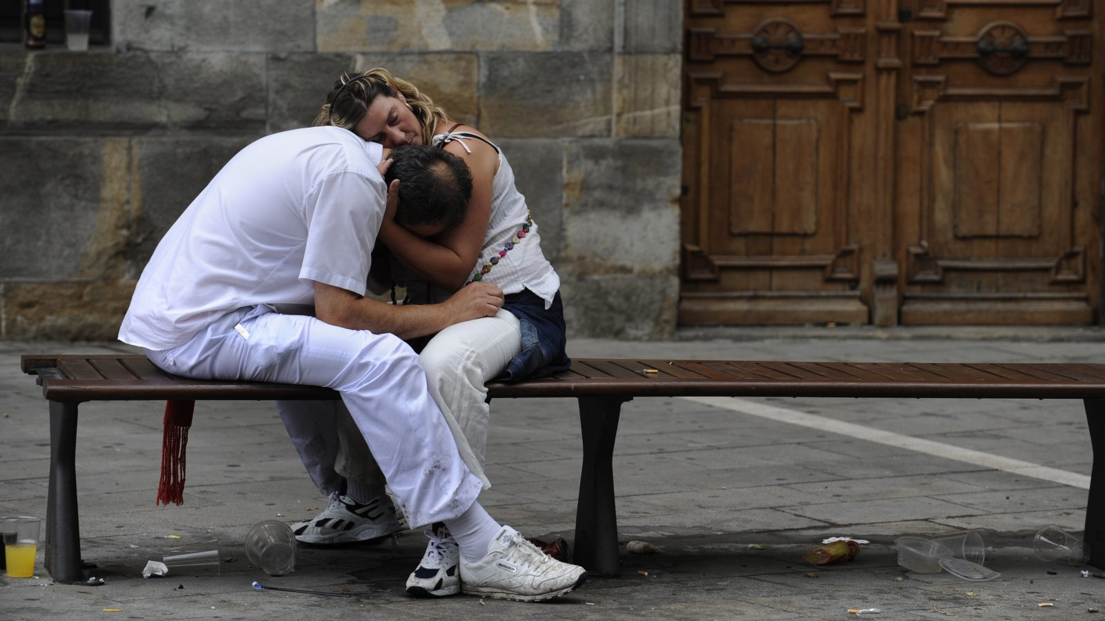 """A sleeping couple embrace on the fifth day of the San Fermin festival in Pamplona July 10, 2011. Visitors to the nine day festival, depicted in Ernest Hemingway's 1926 novel """"The Sun Also Rises"""", take part in activities including The Running Of The Bulls, an early morning half mile dash from the corral to the bullring alongside six bulls destined to die in the afternoon's corrida. This is followed by processions of giant traditional figures, concerts, firebulls, fireworks, and large doses of eating, drinking, dancing and late nights. REUTERS/Eloy Alonso (SPAIN - Tags: SOCIETY) - RTR2OPAY"""