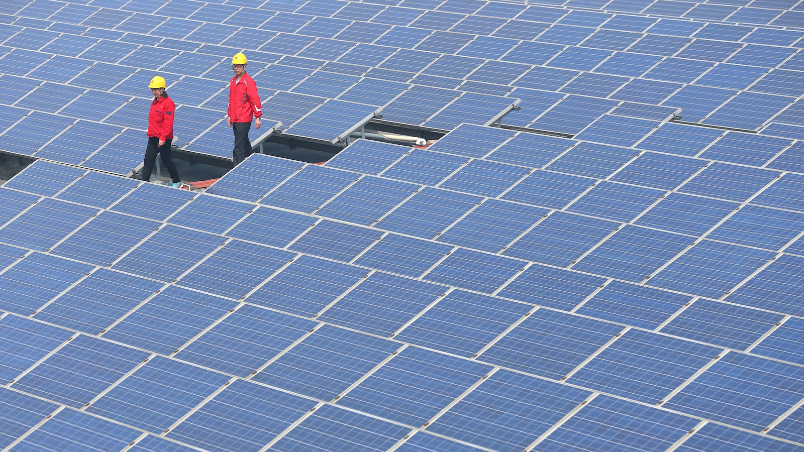 Workers walk past solar panels in Jimo, Shandong Province, China, April 21, 2016. China Daily/via REUTERS ATTENTION EDITORS - THIS IMAGE WAS PROVIDED BY A THIRD PARTY. EDITORIAL USE ONLY. CHINA OUT. NO COMMERCIAL OR EDITORIAL SALES IN CHINA - RTX2AYMN