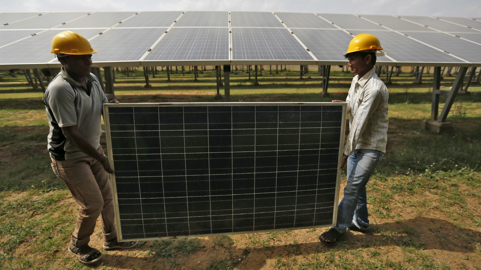 Workers carry a damaged photovoltaic panel inside a solar power plant in Gujarat, India, July 2, 2015. India's $100 billion push into solar energy over the next decade will be driven by foreign players as uncompetitive local manufacturers fall by the wayside, no longer protected by government restrictions on the sector.