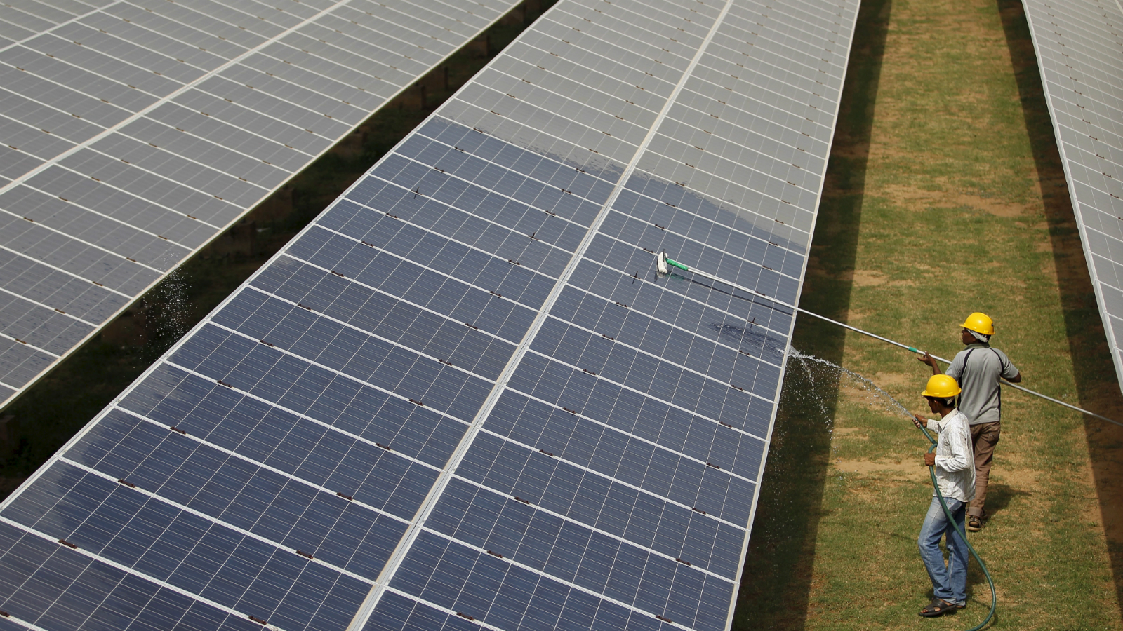 """Workers clean photovoltaic panels inside a solar power plant in Gujarat, India, in this July 2, 2015 file photo. The likely collapse of SunEdison Inc's solar project in India, the first of 32 planned """"ultra mega"""" complexes, could delay Prime Minister Narendra Modi's goal to increase renewable energy fivefold by several years and probably cost consumers more."""