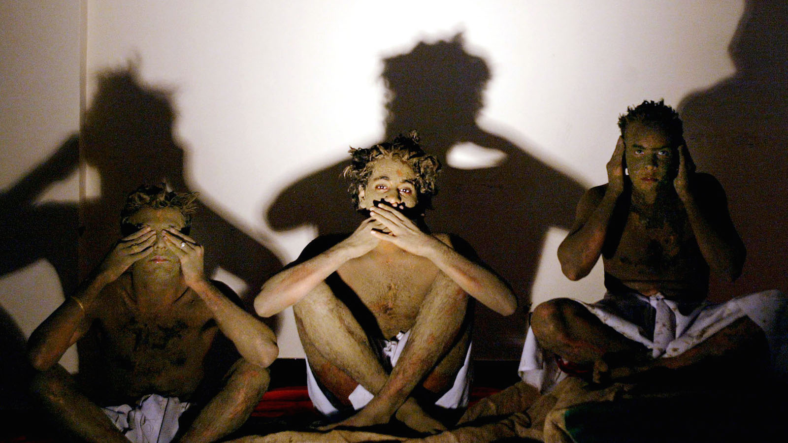 """Indian college students demonstrate the concept of """"hear no evil, see no evil, speak no evil', principles espoused by Mahatma Gandhi, during an event to mark the 55th anniversary of the death of Gandhi in Bombay January 30, 2003. Students from a city college reenacted several scenes from Gandhi's freedom struggle against the British colonial rule. REUTERS/Arko Datta  AD/CP - RTR11S7S"""