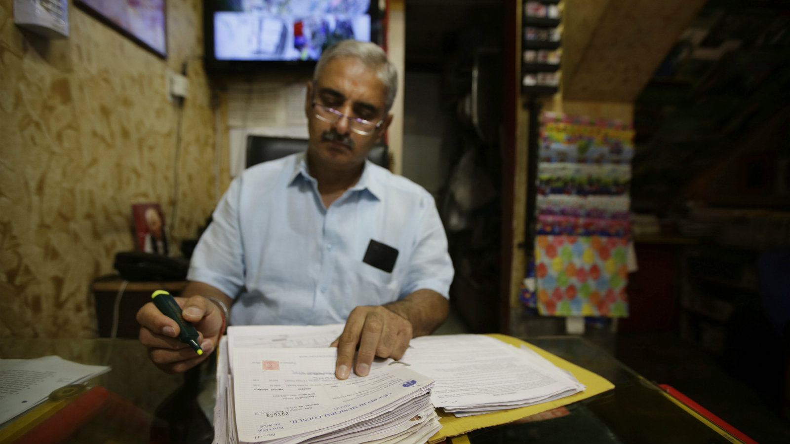 In this June 15, 2017 photo, Sanjiv Mehra, a toy shop owner checks his ledger at his shop in Khan Market, New Delhi, India. Indian businesses are in a tizzy trying to comply with a long-awaited reform in the country's sales regime. The government says the Goods and Services Tax going into effect July 1 will boost the economy by streamlining business within a single market. Traders and business owners are still trying to figure out how it will work