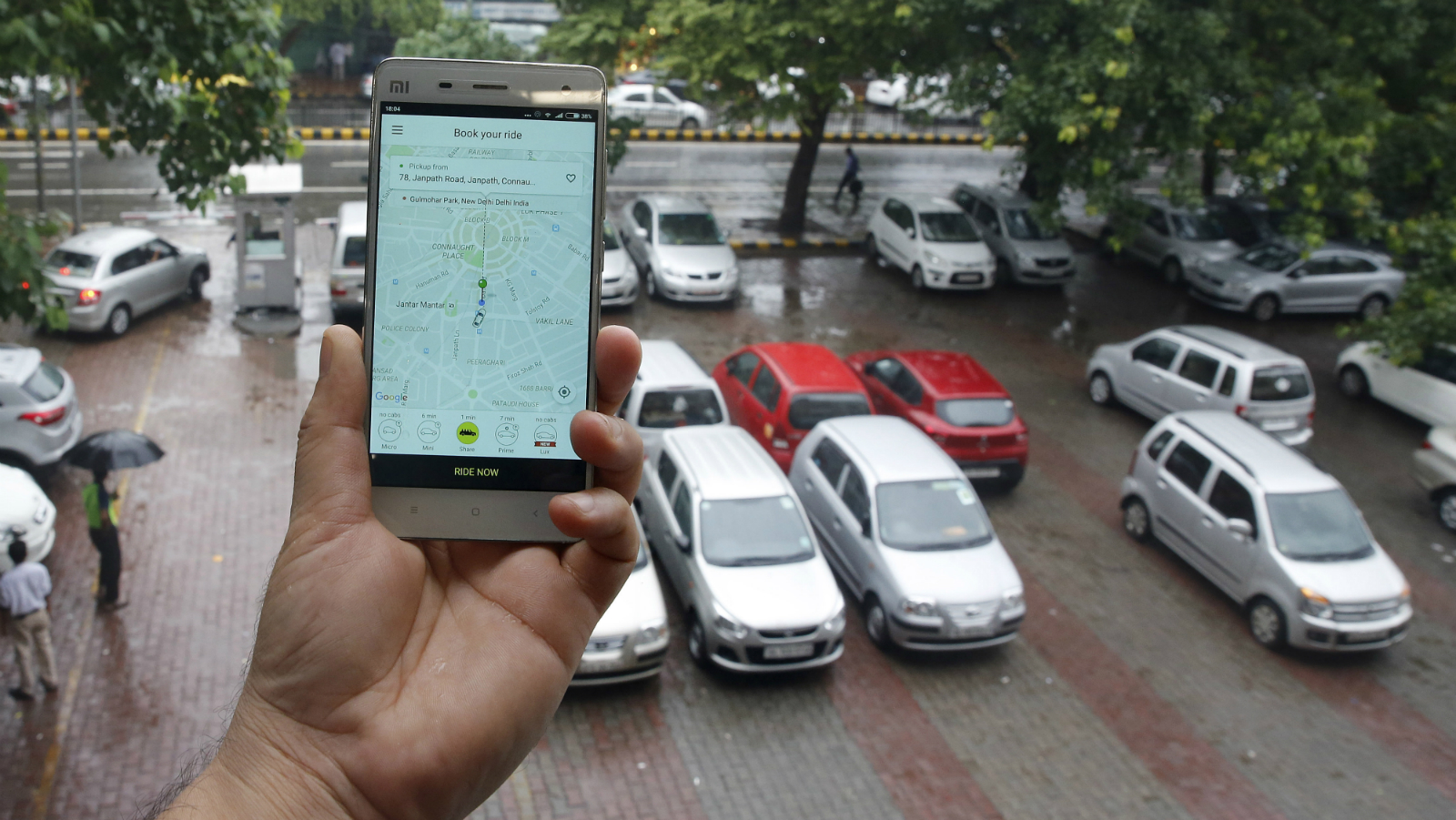 An Indian man holds a smartphone with the Ola app to book a taxi in New Delhi, India, 29 July 2016. According to local news reports, App-based taxi services made considerable profits during recent auto rickshaw and taxi strikes that were directed against App-based taxi services.  Scene