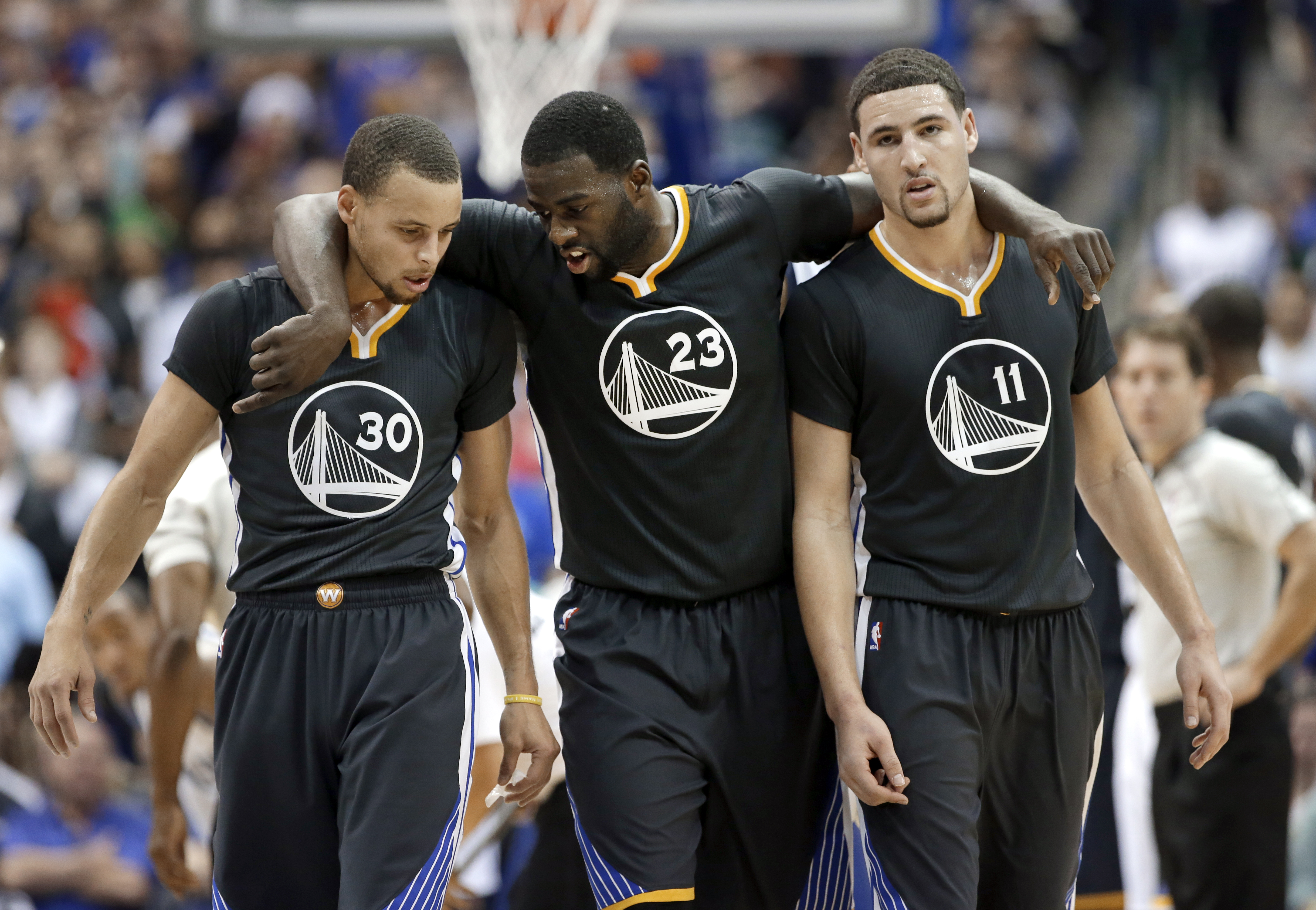 Golden State Warriors guard Stephen Curry (30), Draymond Green (23) and Klay Thompson (11) walk up court during the second half of an NBA basketball game against the Dallas Mavericks, Saturday, Dec. 13, 2014, in Dallas. Curry had 29-points, Green had 20-points and Thompson had 25-points in the 105-98 Warriors win. (AP Photo/Tony Gutierrez)