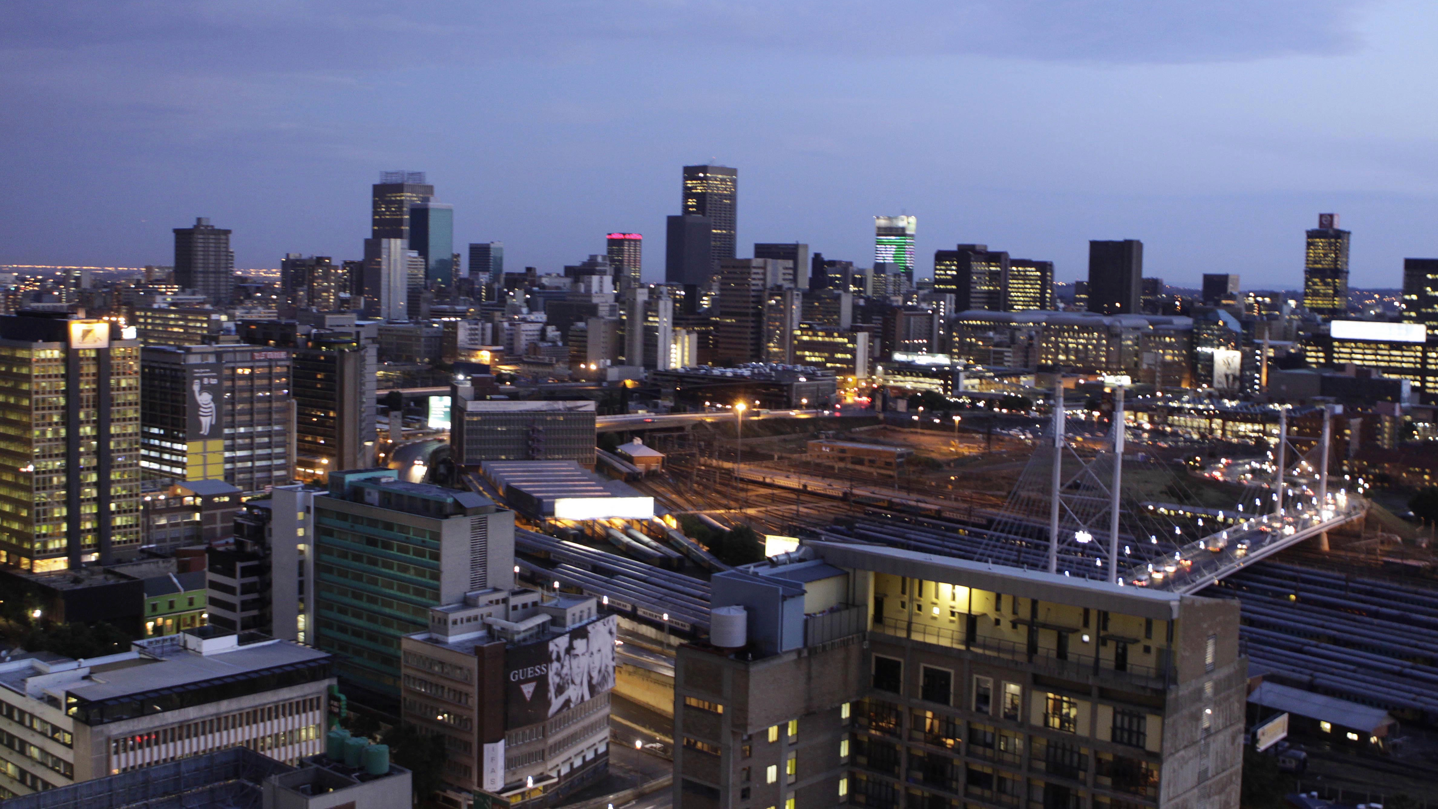 This photo taken Friday, Nov. 18, 2011 shows the city lights, after sunset, in Braamfontein, Johannesburg. Johannesburg dates its beginnings to the discovery of gold in 1886. Its downtown, where skyscrapers tower over deep mines, was abandoned by business in recent decades, and squatters turned the office towers into high-rise slums. But now, as the city celebrates its 125th birthday, creative South Africans are seeing gold in warehouses and cheap office space, and they're revitalizing neighborhoods with galleries, museums, shops, studios, clubs and restaurants.   ( AP Photo/Denis Farrell)