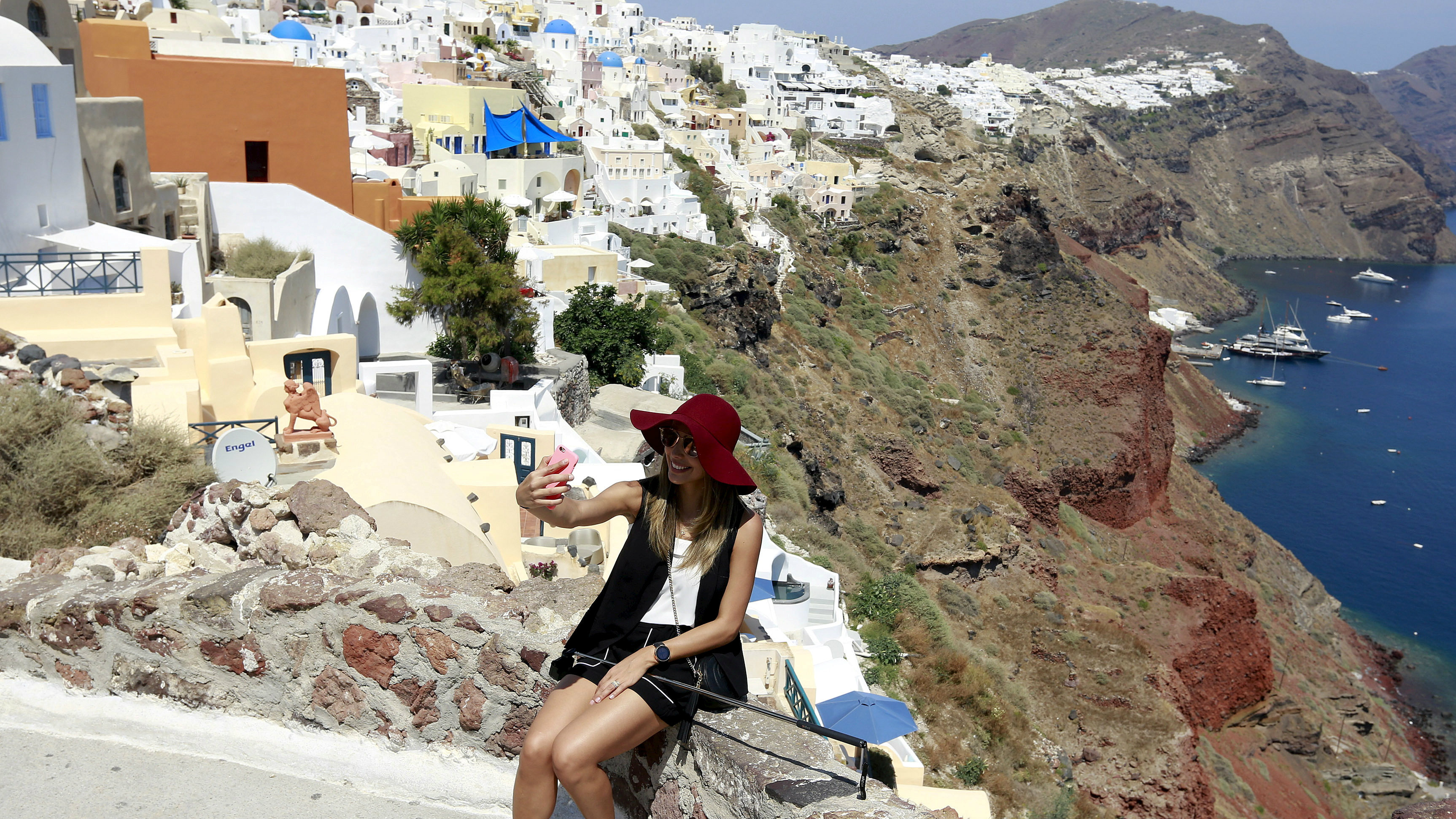 A tourist takes a selfie in the village of Oia on the Greek island of Santorini, Greece.