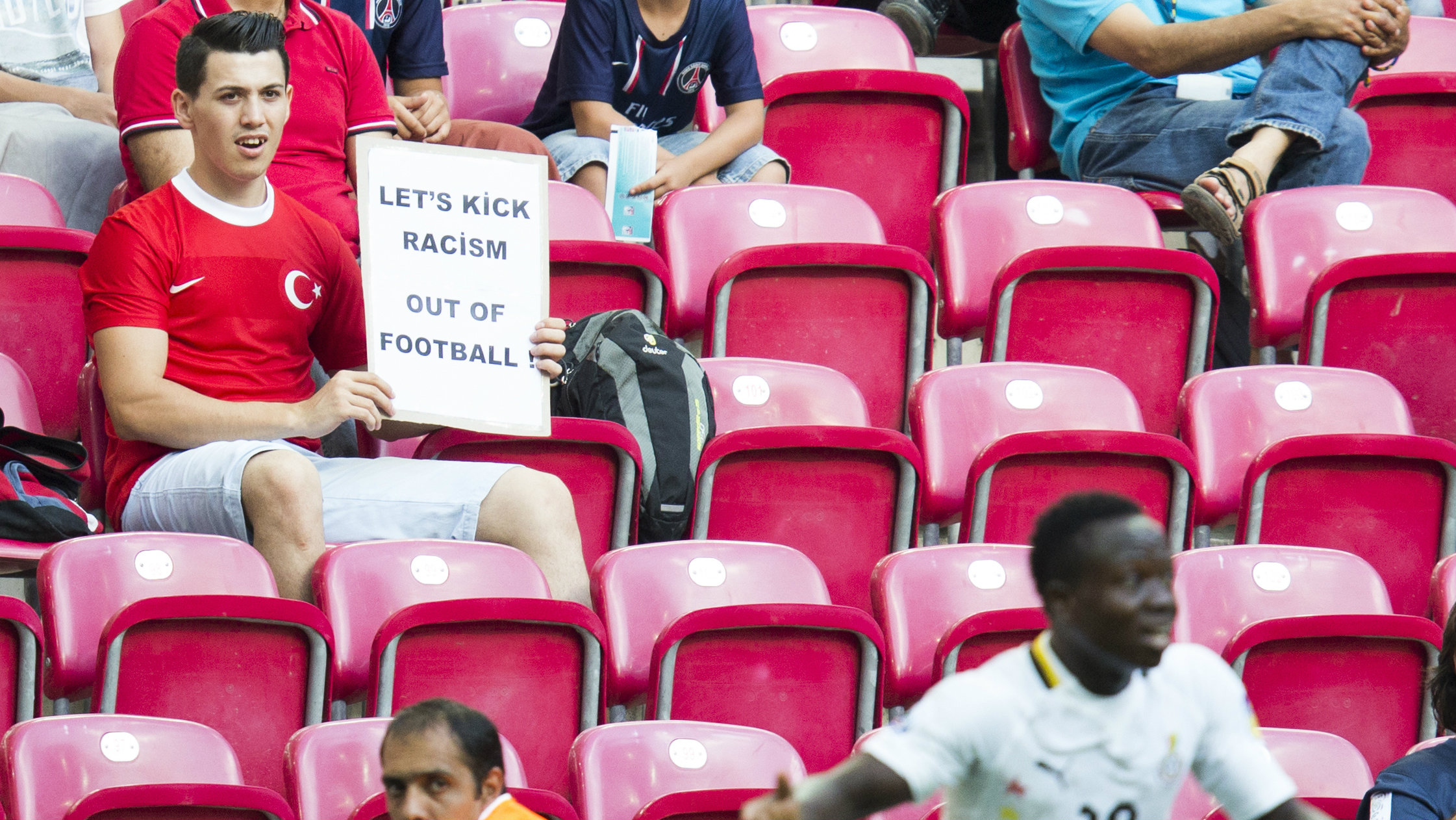 """A spectator displays a banner reading """"let's kick racism out of football"""" as Ghana's Moses Odjer, foreground right, gestures during the Under-20 World Cup Group A soccer match between France and Ghana, in Istanbul, Turkey, Friday, June 21, 2013. France won the match 3-1"""