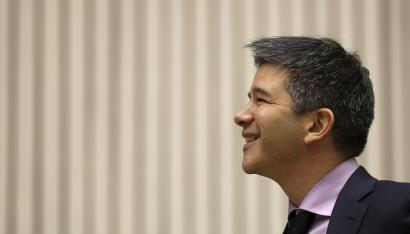 Uber CEO Travis Kalanick smiles as he addresses a gathering during a conference.
