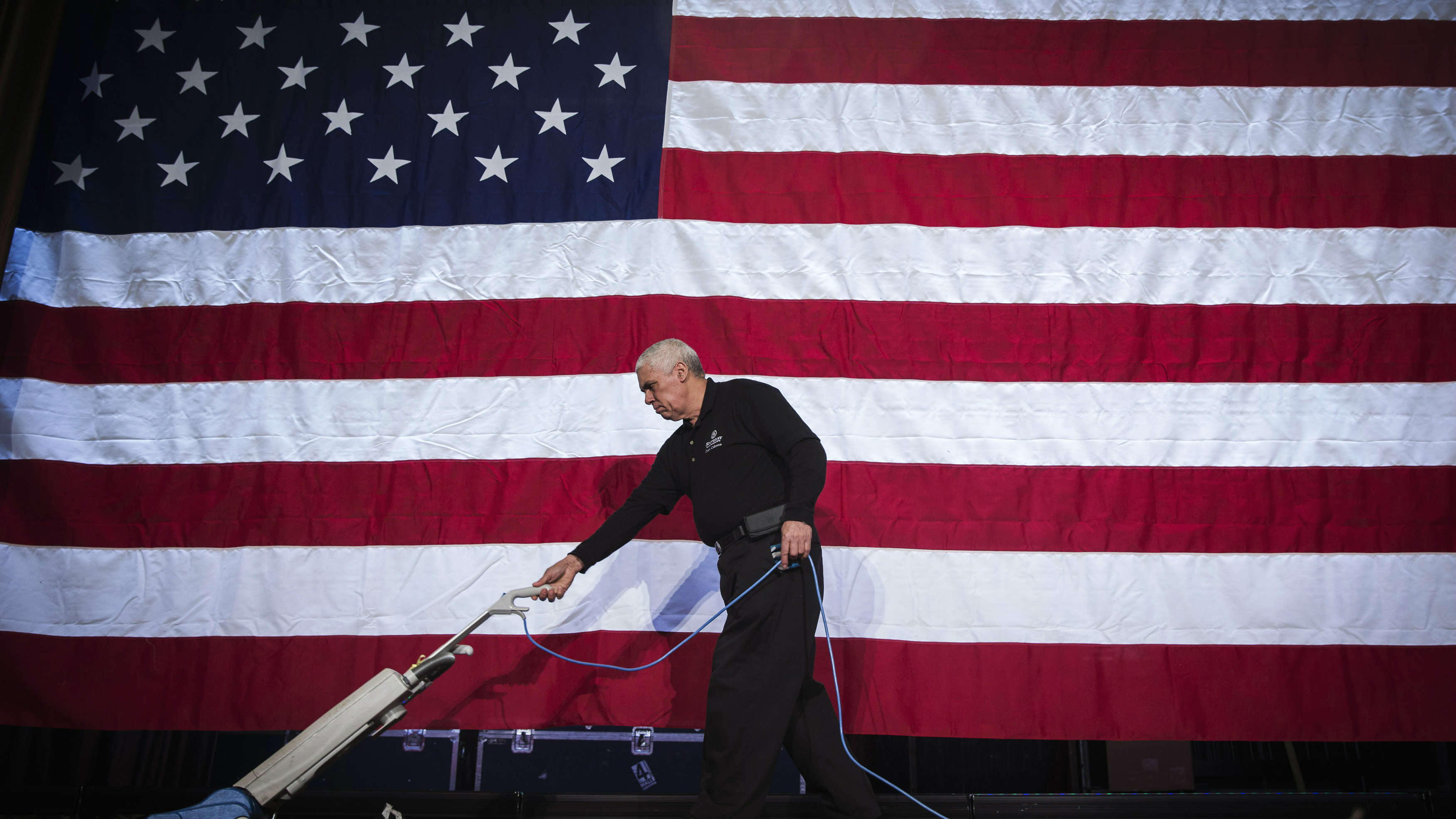 Worker cleans a stage in front of a US flag