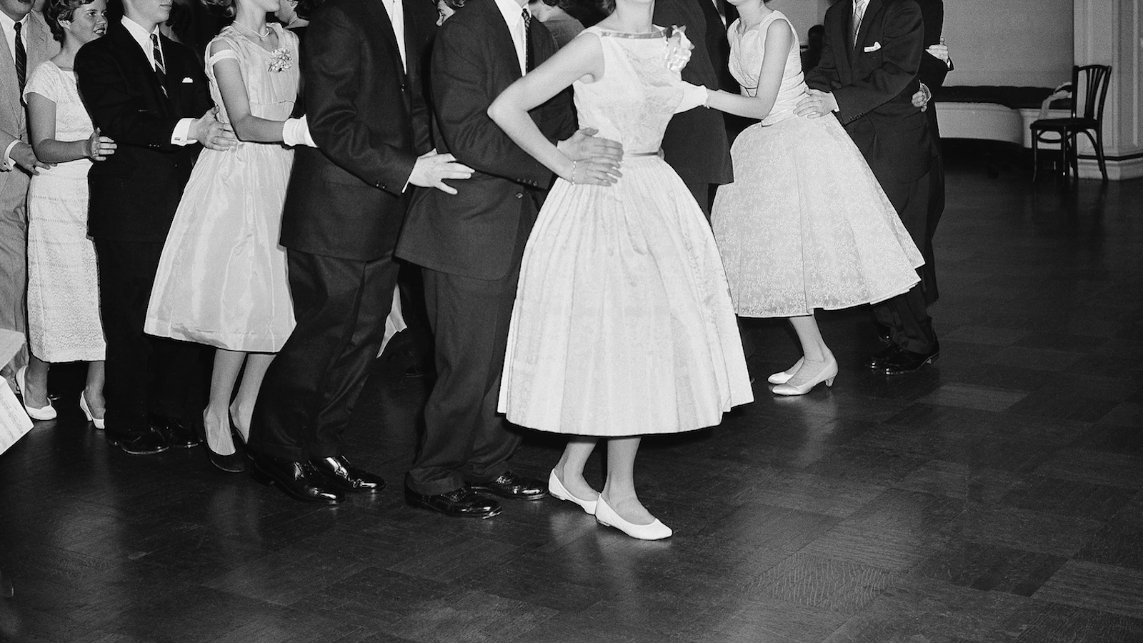 """Young guests do a """"bunny hop"""" at a dance for teenagers at the Congressional Club in Washington on May 23, 1957. (AP Photo/Byron Rollins)"""
