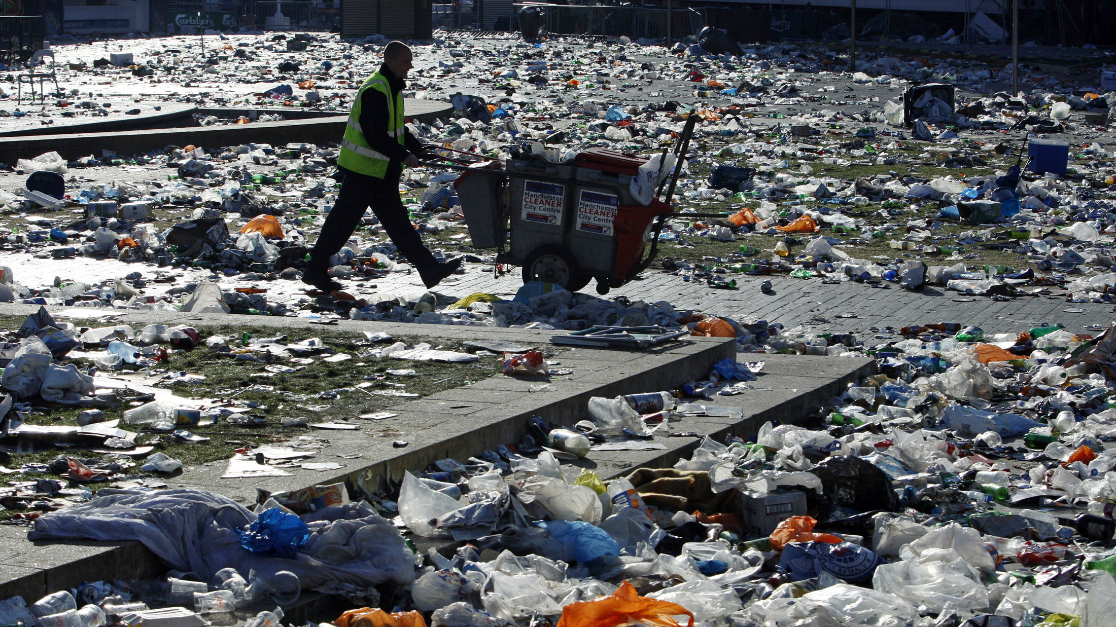 A street cleaner walks through rubbish in Piccadilly Gardens, after the Rangers lost to Zenith St. Petersburg during their UEFA Cup final in central Manchester, northern England, May 15, 2008.