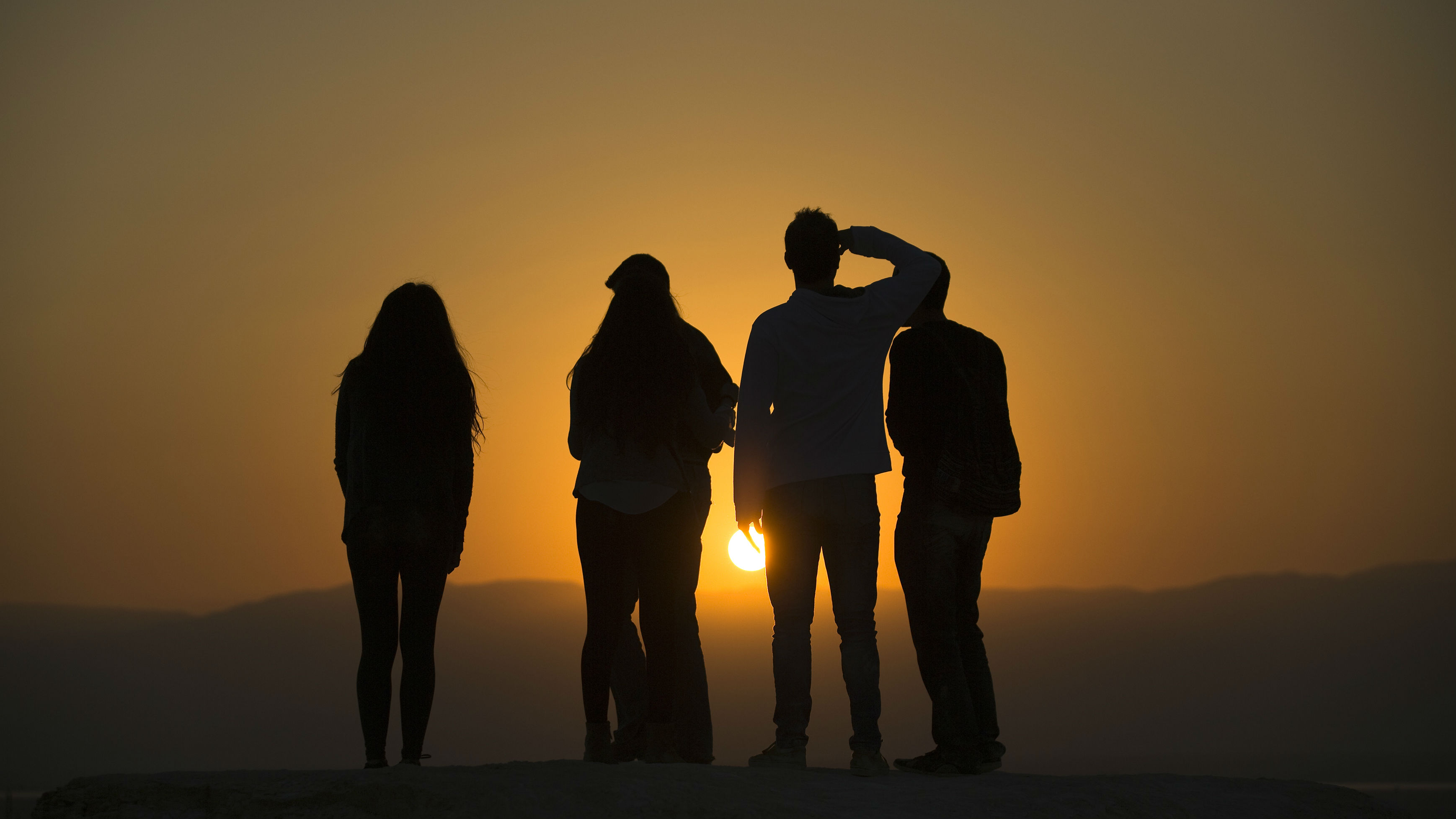 People watch the sunrise after Dead Sea Rave -424, an international electronic music festival at the foot of Masada mountain, along the shores of the Dead Sea, October 24, 2014.