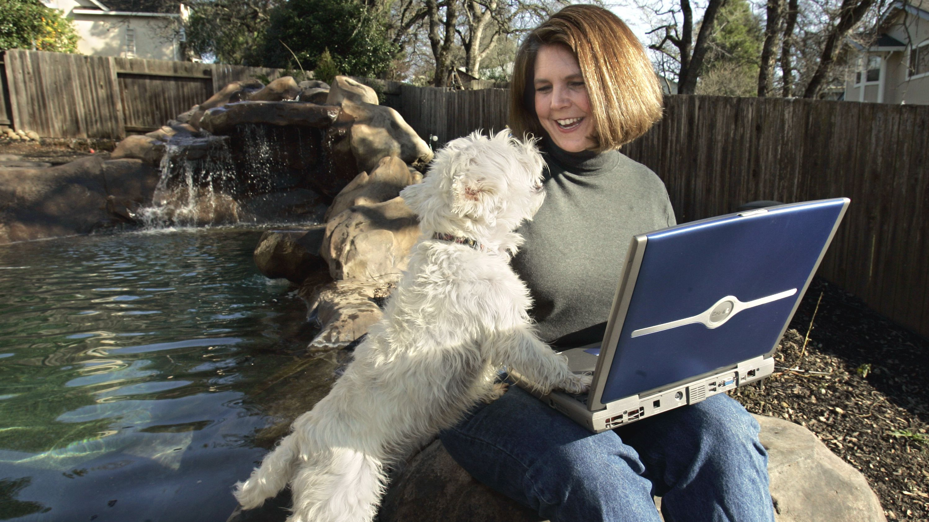 ** ADVANCE FOR TUESDAY, FEBRUARY 7 ** Cheryl Demas,creator and editor of wahm.com, an online magazine for work-at-home mothers, takes a break to pet the family dog, Yoshhi, while working outside by the swimming pool at her Folsom, Calif., home, Friday, Feb. 3, 2006. Using her laptop to do most of her work, Demas moves around her home to do her work and instead of being confined to one location.(AP Photo/Rich Pedroncelli)