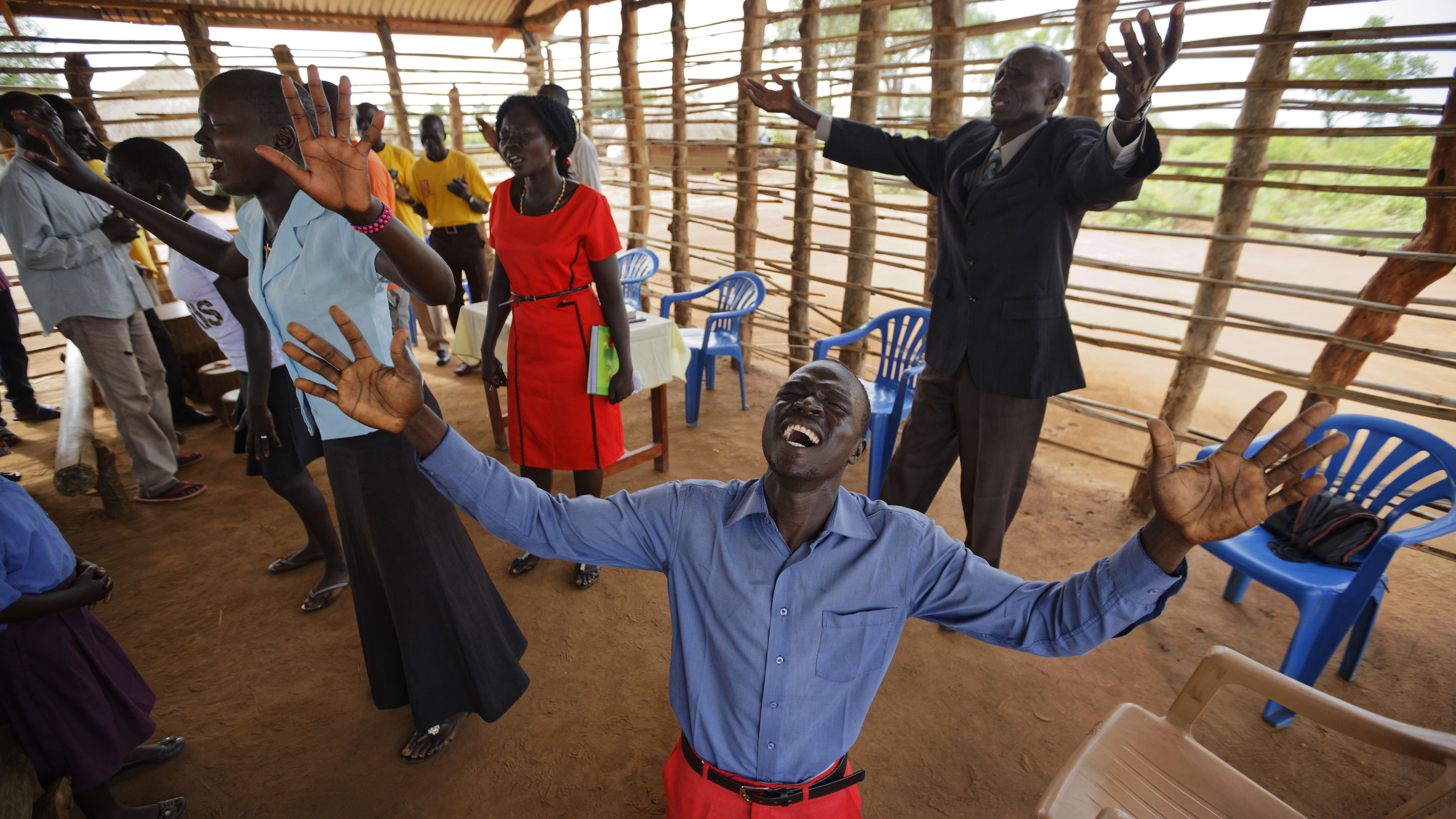 In this photo taken Sunday, June 4, 2017, preacher Daniel Rasash falls to his knees and weeps in prayer, at the Yoyo Pentecostal Church in Bidi Bidi refugee settlement in northern Uganda. The South Sudanese refugees meet in open-air churches rigged from timber with seats made only from planks of wood or logs drilled into the ground, yet these churches for the born-again Christians are oases of joy among the daily humiliations that come with rebuilding their lives.