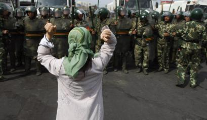 In this July 7, 2009 file photo, a Uigher woman demands the return of members from her community before a group of paramilitary police officers when journalists visited the area in Urumqi in western China's Xinjiang province. Nearly a year after the worst communal riots in China's far west in more than a decade, stories of asylum seekers interviewed by The Associated Press are among the few accounts to emerge of how some Uighurs managed to get out amid a government crackdown. (AP Photo/Ng Han Guan, File)