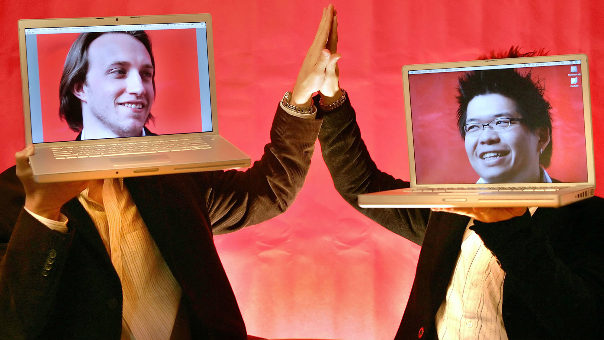 YouTube co-founders Chad Hurley and Steven Chen pose with their laptops