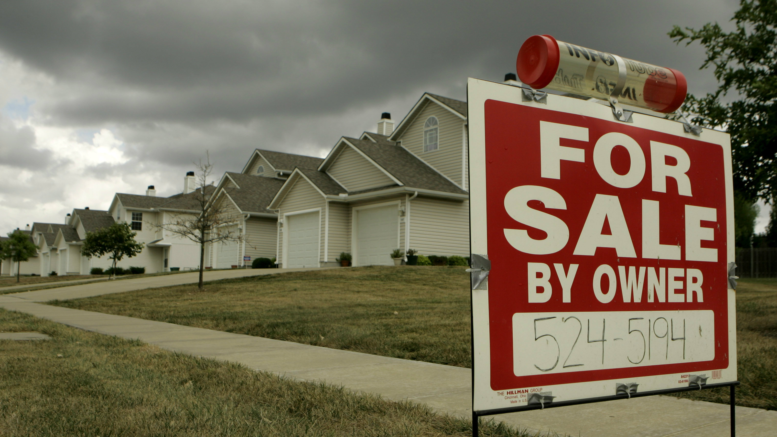 """For Sale"" sign in front of a row of houses"