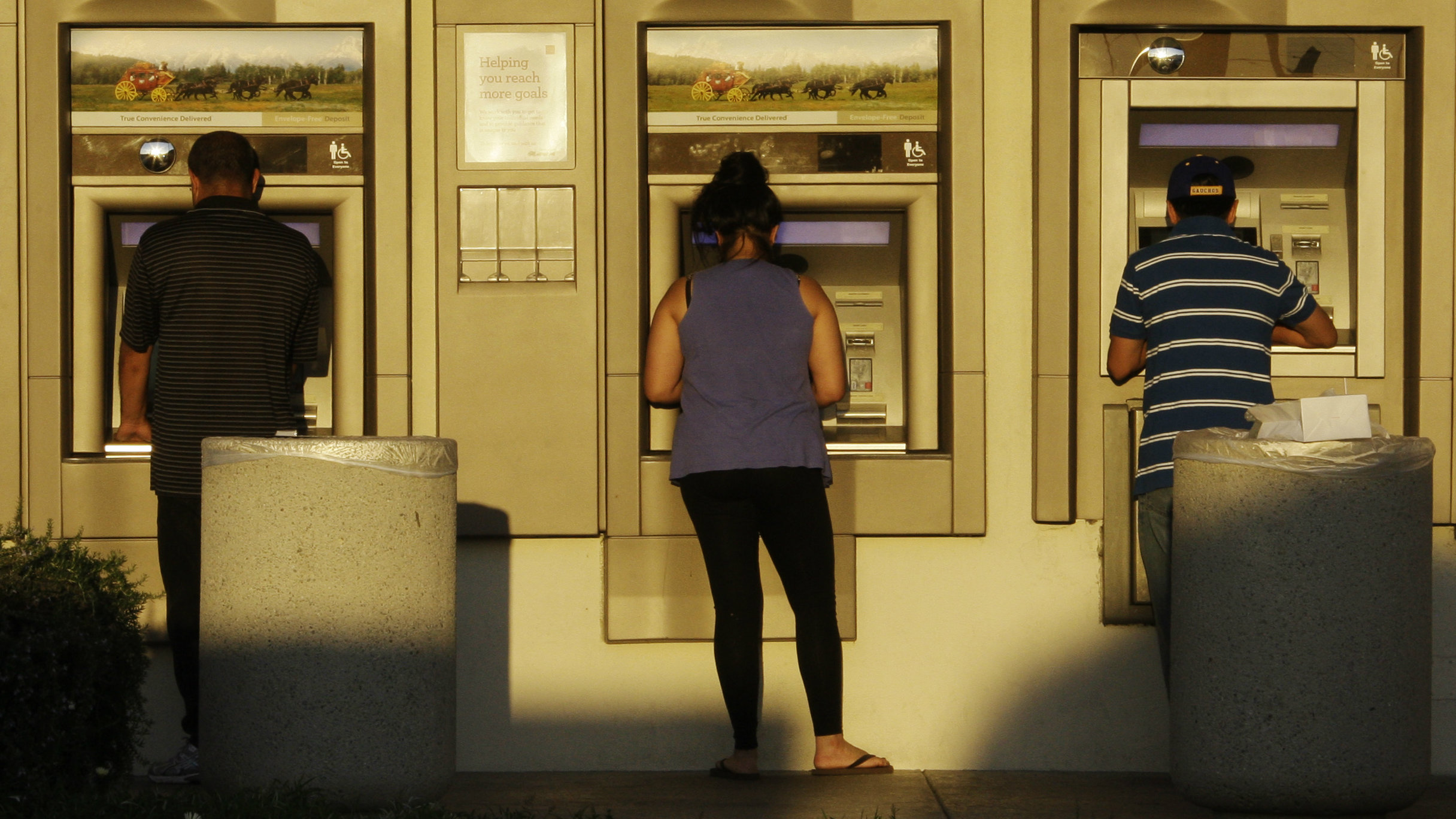 Bank customers getting cash at a row of ATMs