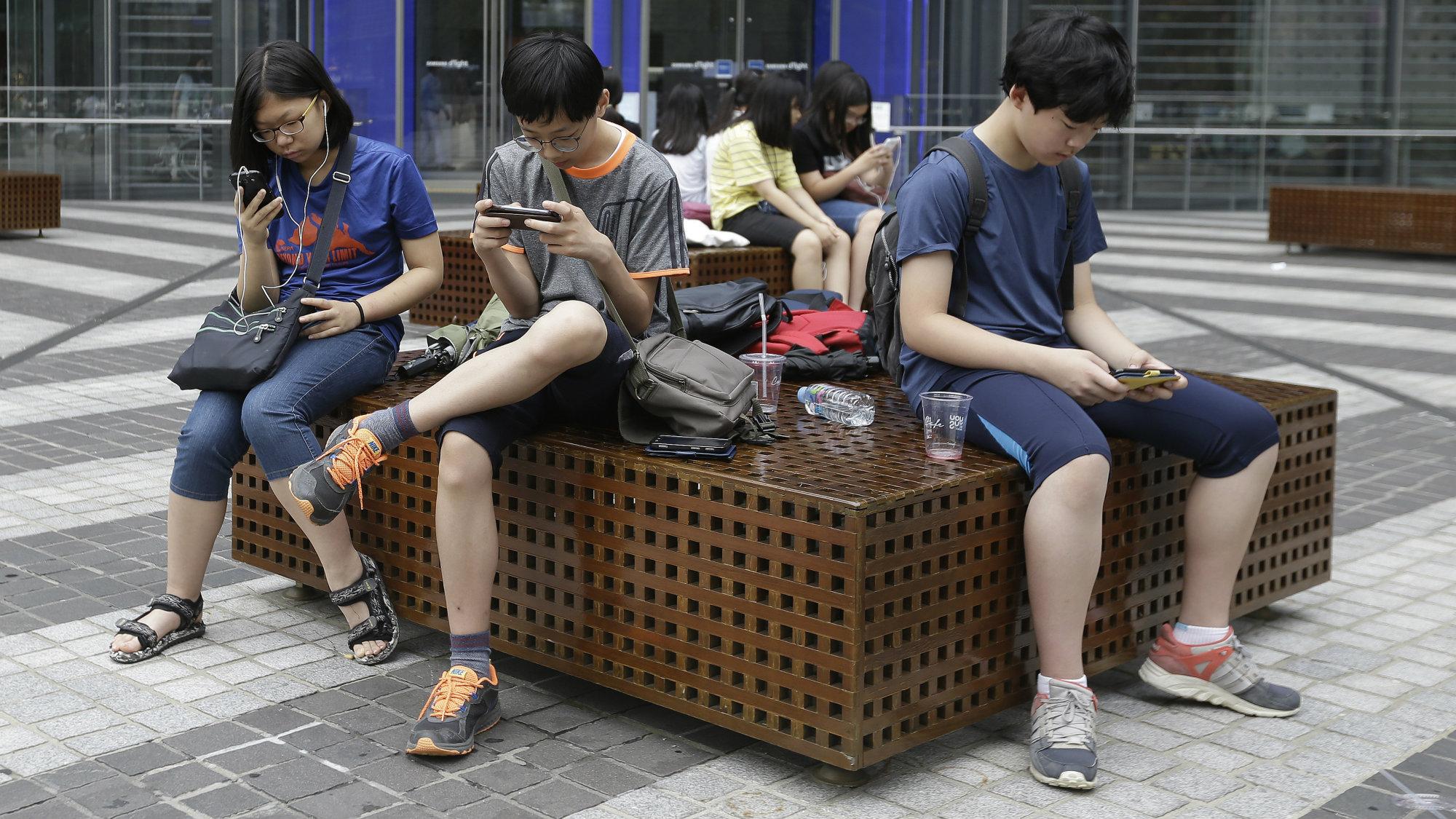 Teenagers looking at their mobile phones
