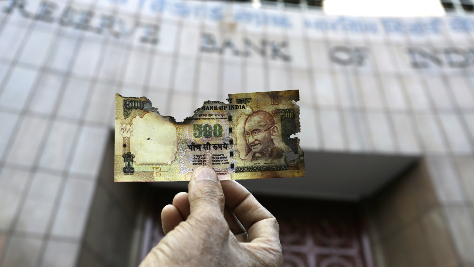 A man holds a charred facsimile of the discontinued Indian currency 500 note after a protest by a traders association demanding adequate arrangement to exchange discontinued currency notes outside Reserve Bank of India in Kolkata, India, Wednesday, Nov. 16, 2016. India announced a week ago that it was withdrawing 500 and 1,000 rupee notes as legal tender to fight corruption and tax evasion. However, people are allowed a onetime swap of 4,000 rupees ($59) at any bank in exchange for smaller notes to meet immediate needs