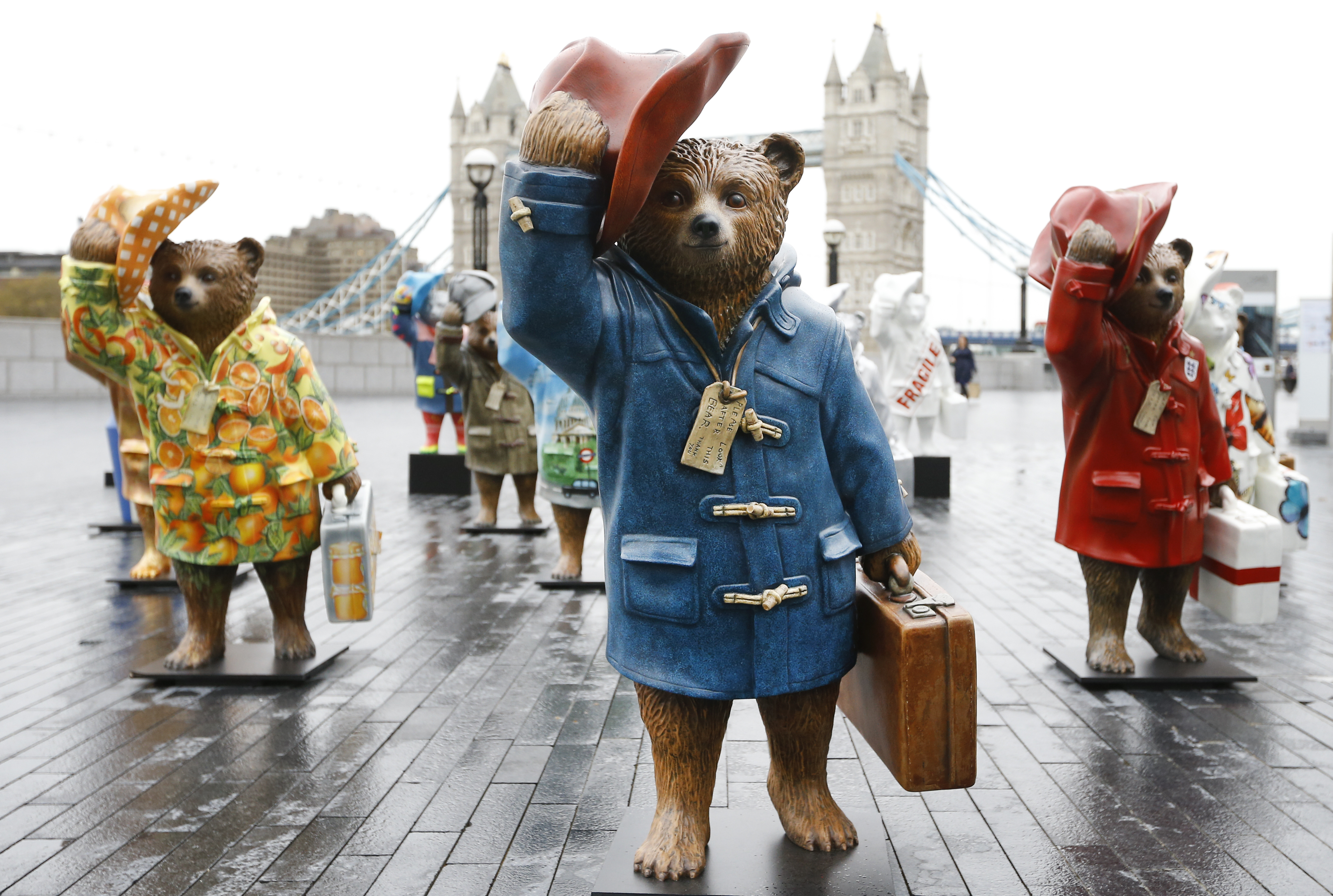 Statues of Paddington Bear stand near Tower Bridge in London, Monday, Nov. 3, 2014. The bear was one of many statues at the press launch for The Paddington Trail, which will run from Nov. 4. Fifty Paddington statues will be placed across the capital ahead of the release of the film 'Paddington' in UK cinemas on Nov. 28, 2014. The statues all decorated by various celebrities will be auctioned in Dec. to raise money for the NSPCC and its ChildLine service.