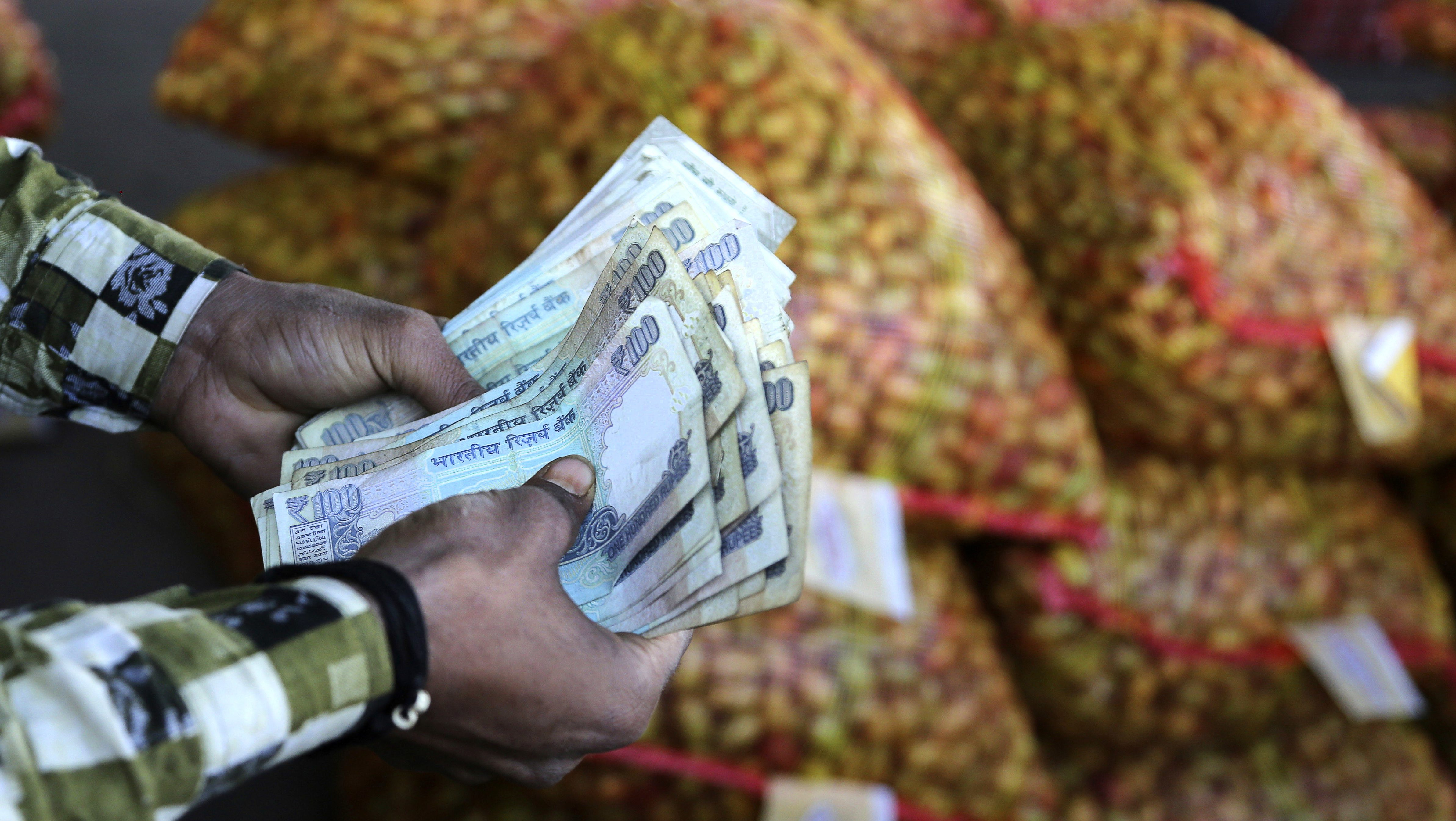 An Indian trader counts rupees at wholesale vegetables market on the outskirts of Jammu, India, Monday, March 6, 2017. India's economy registers a faster-than-expected growth of 7 per cent in fiscal third quarter 2016-17, notwithstanding the demonetization of high-value banknotes in November that caused immense hardship to small businesses dependent on cash transactions.