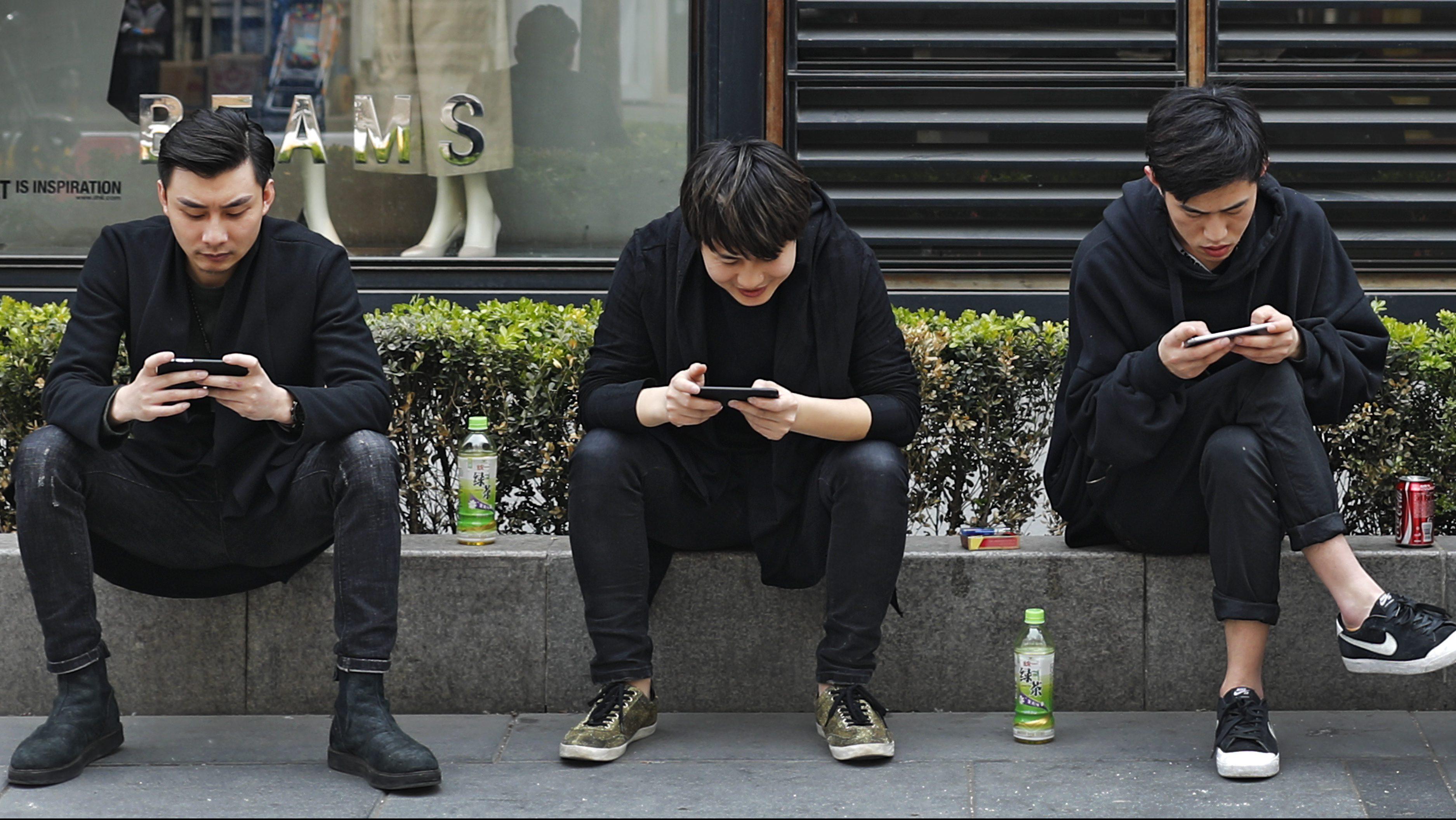 Three men use their smartphones