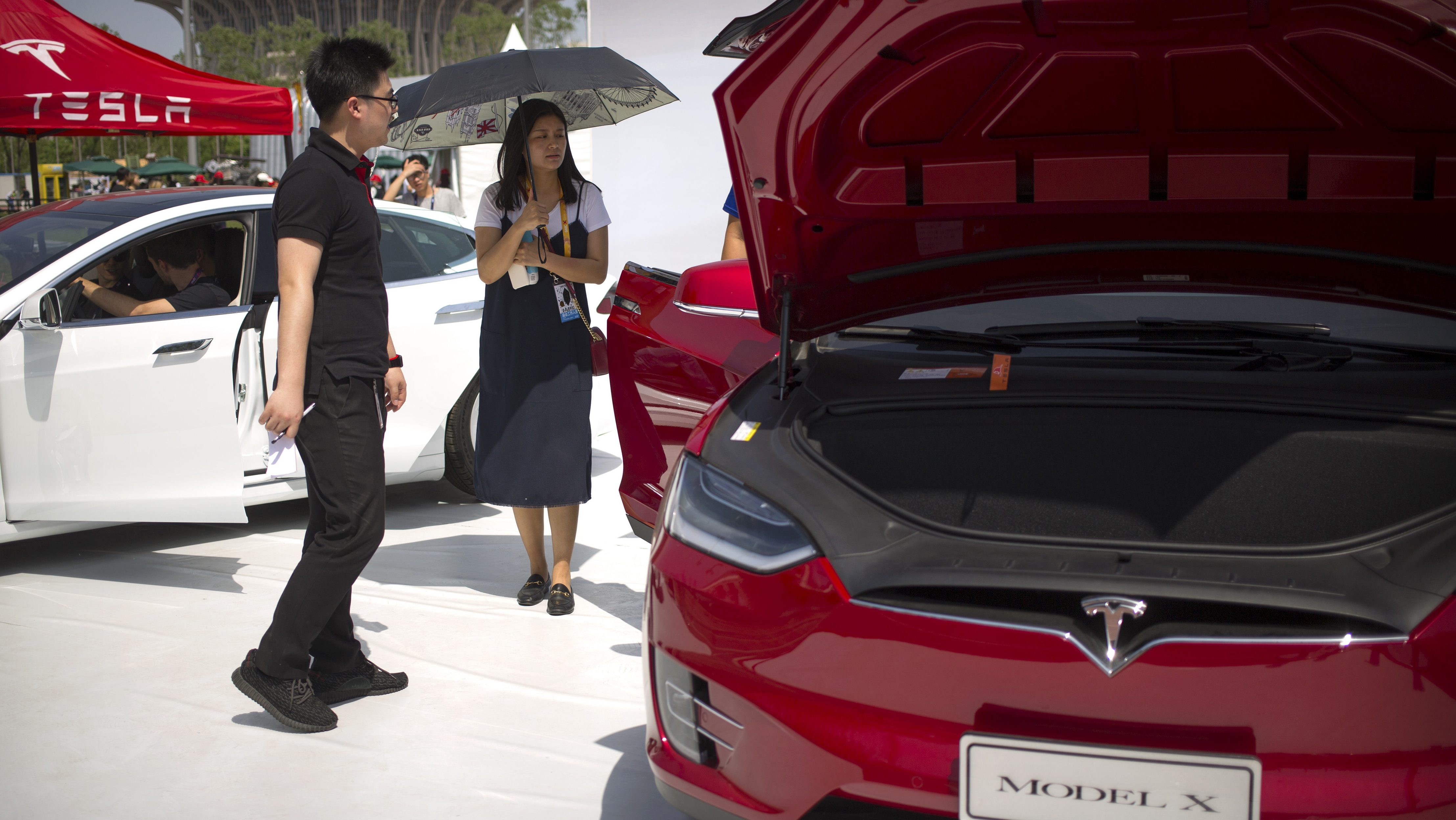 A visitor holds an umbrella as she looks at a Tesla Model X car on display at the G Festival, part of the Global Mobile Internet Conference (GMIC) in Beijing, Saturday, April 29, 2017. (AP Photo/Mark Schiefelbein)