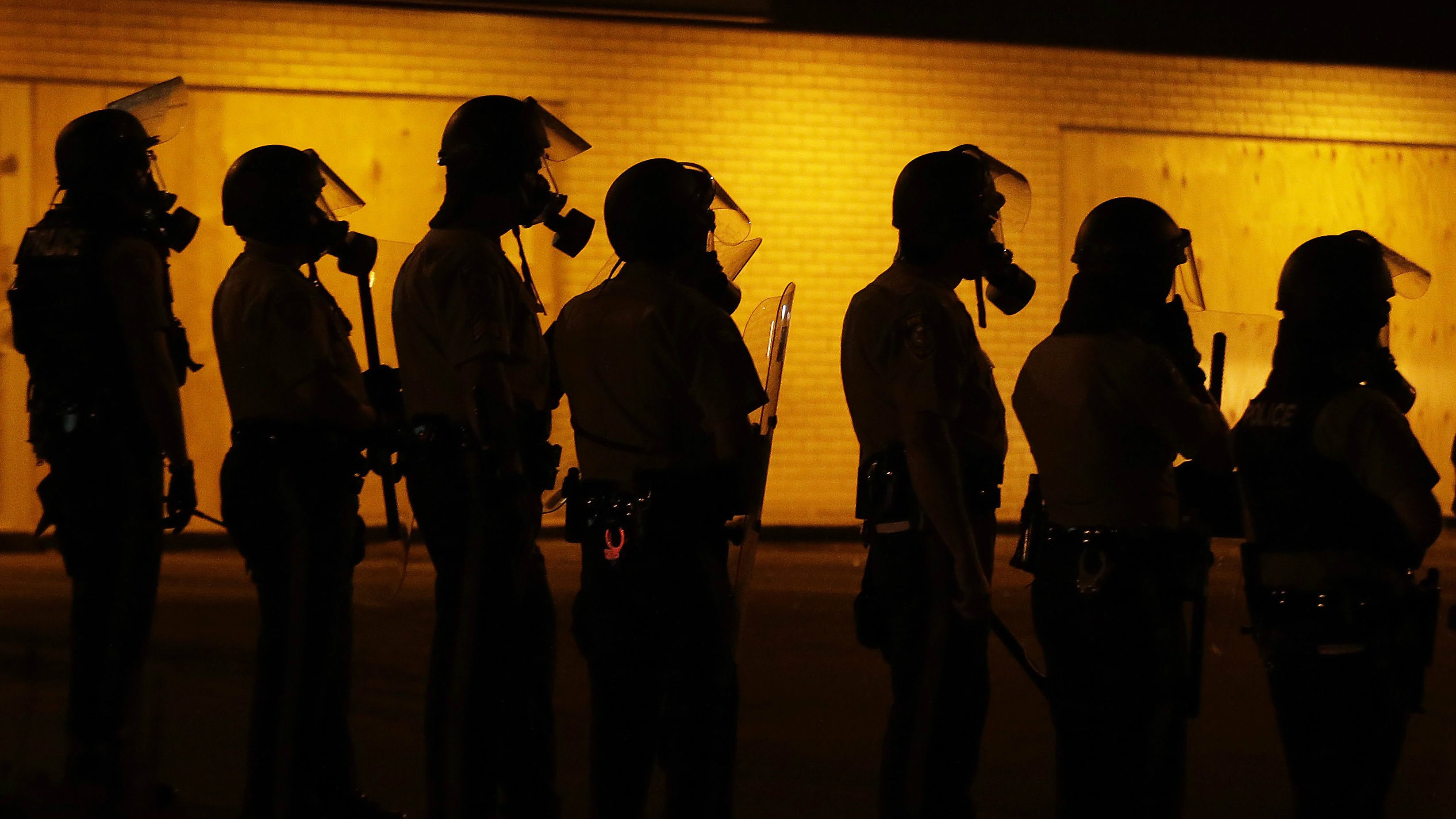 Police wait to advance after tear gas was used to disperse a crowd during a protest in 2014 for Michael Brown in Ferguson, Mo. unless